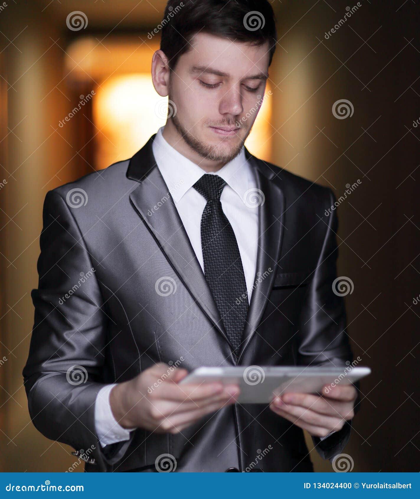 Close up. portrait of elegant businessman with digital tablet on office background