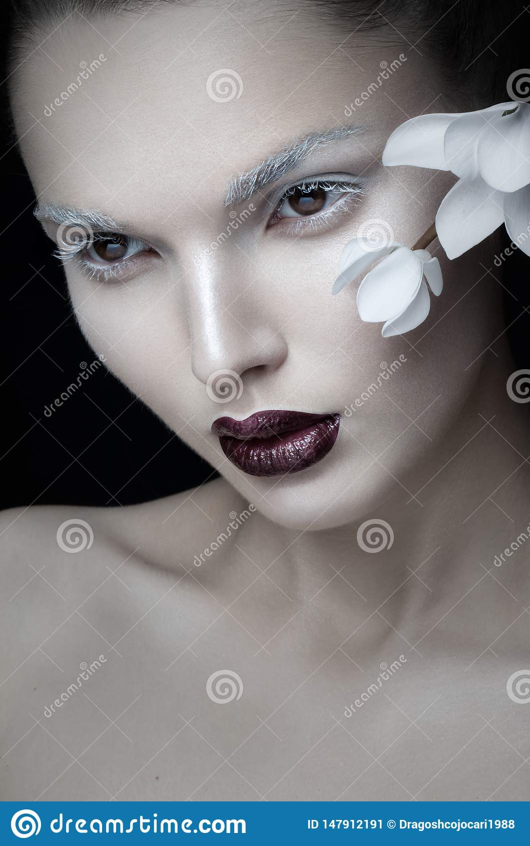 Frontal view of beauty portrait artistic makeup, burgundy lips, face, near white flower, isolated on black background.