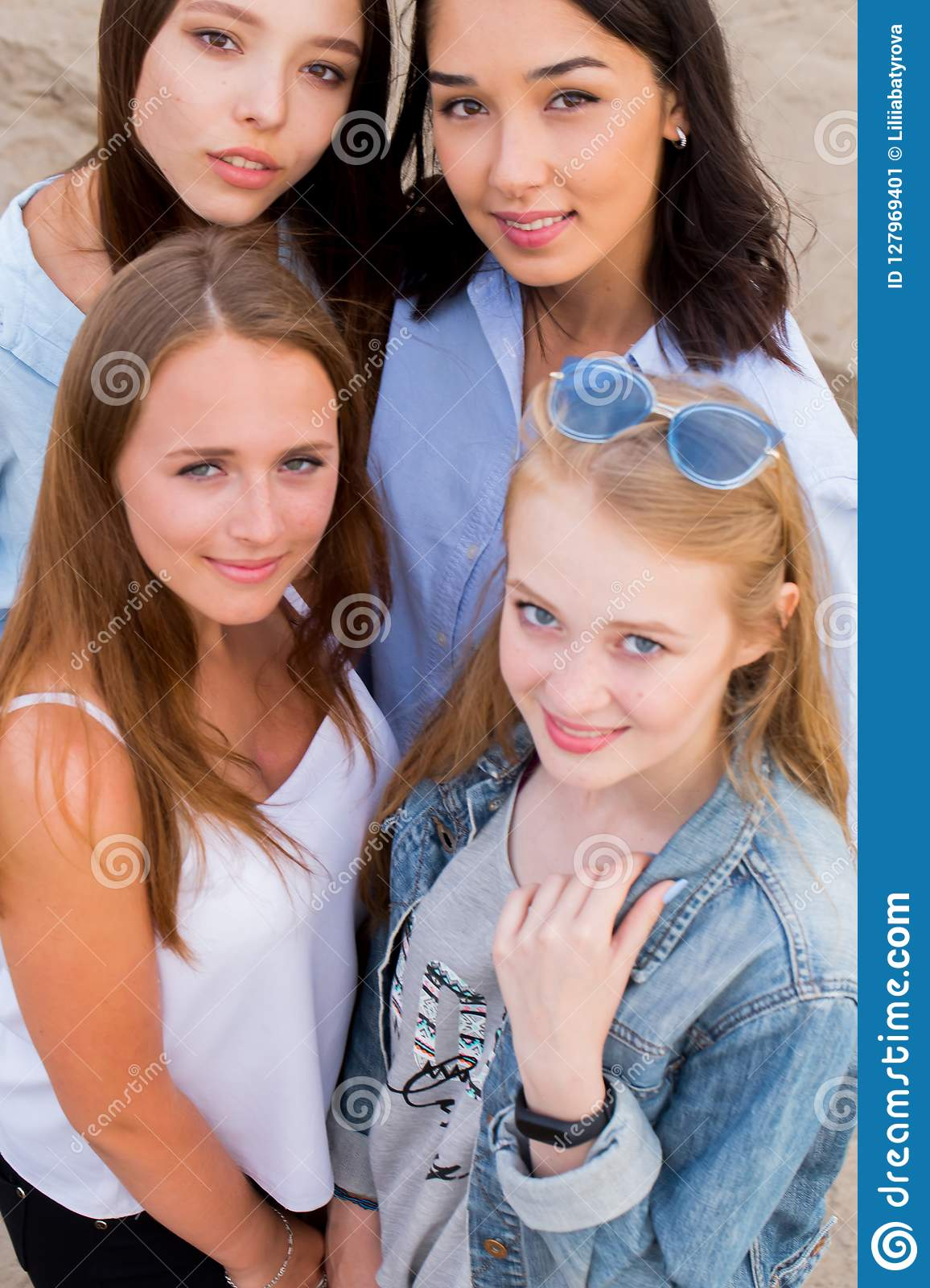 Close-up portrait of four young beautiful girlfriends in summer on the beach