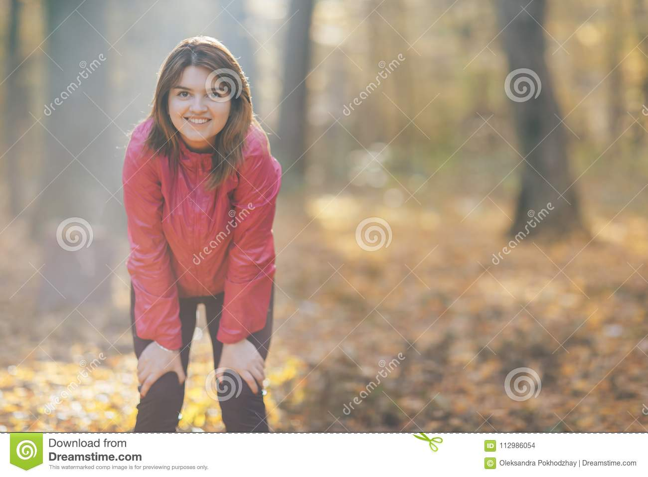 Close-up portrait of a girl who trains in the morning autumn park