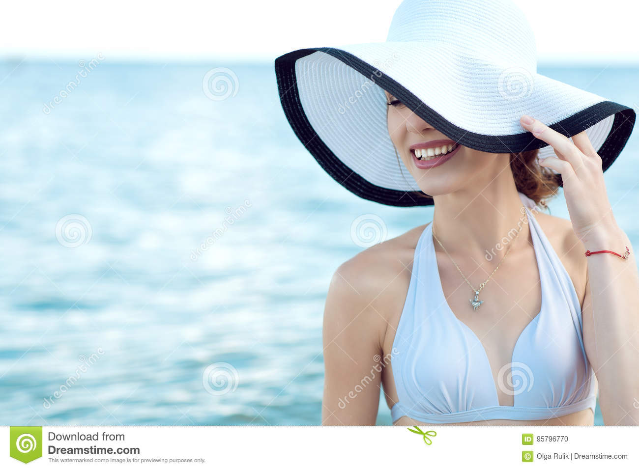 Close up portrait of gorgeous glam smiling lady hiding the half of her face behind the wide brim hat