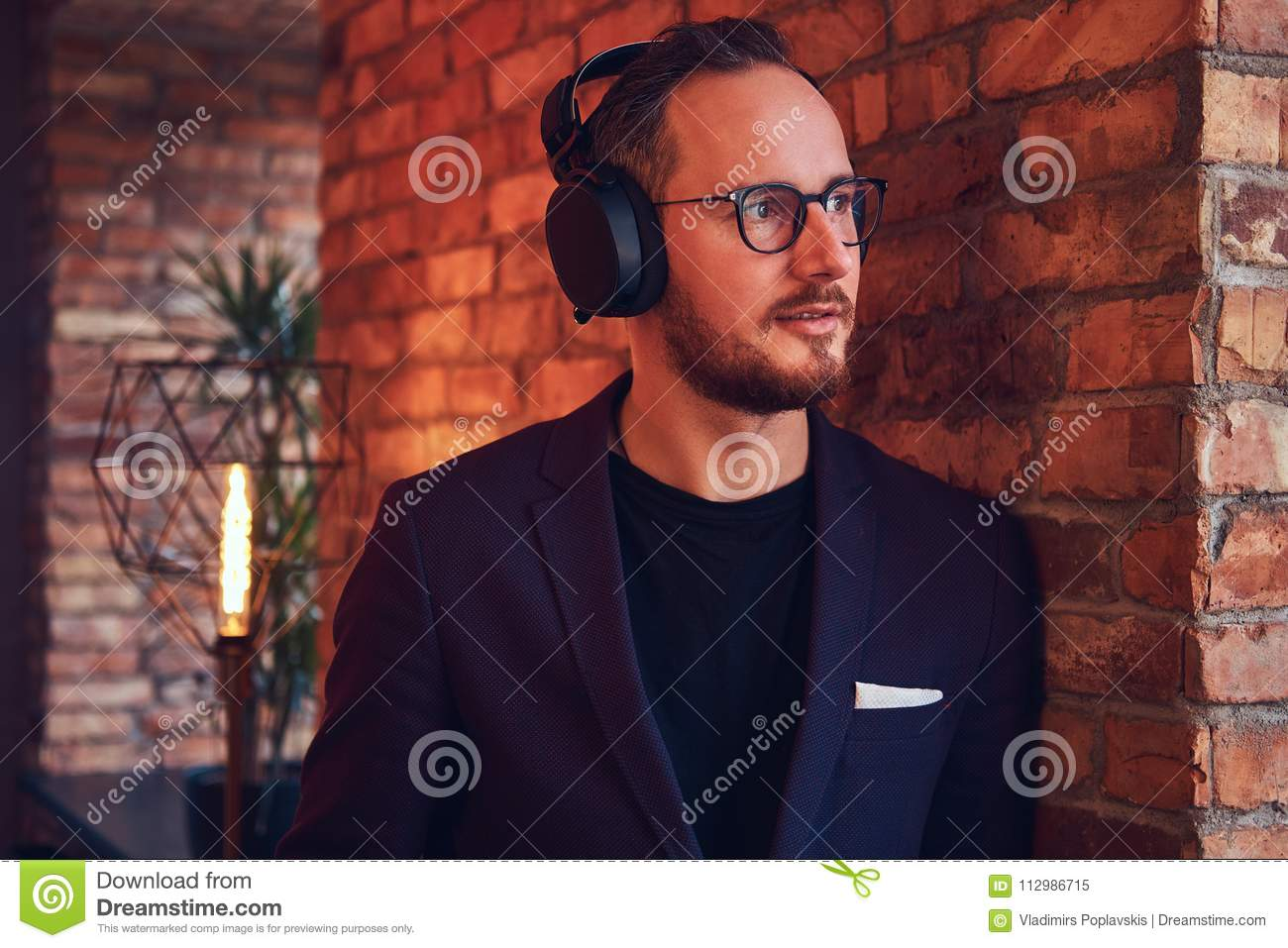 Close-up portrait of a handsome bearded male wearing stylish suit listening music in headphones against a brick wall.