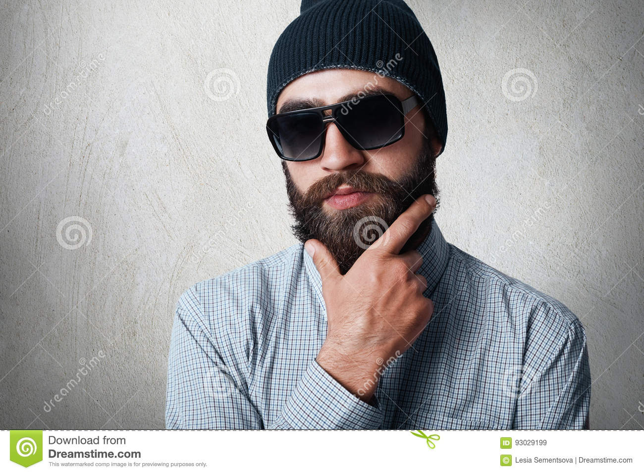 Close-up portrait of handsome bearded man wearing stylish black cap, checked shirt and sunglasses holding his hand on thick beard