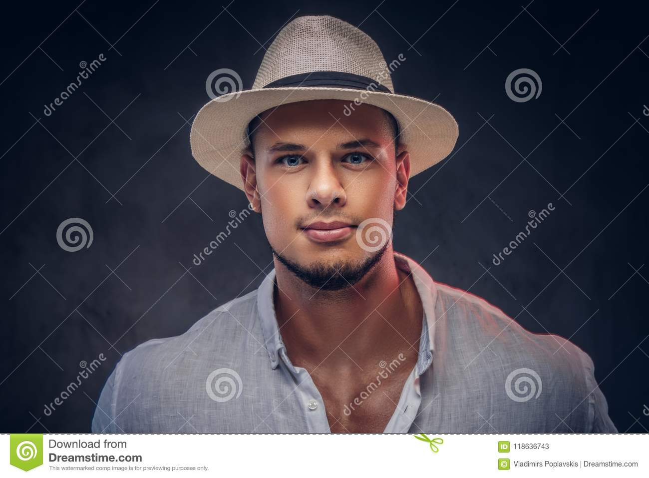 0db357f5fe54de Close-up portrait of a handsome fashionable bearded man in a white shirt  and panama hat. Isolated on dark background.