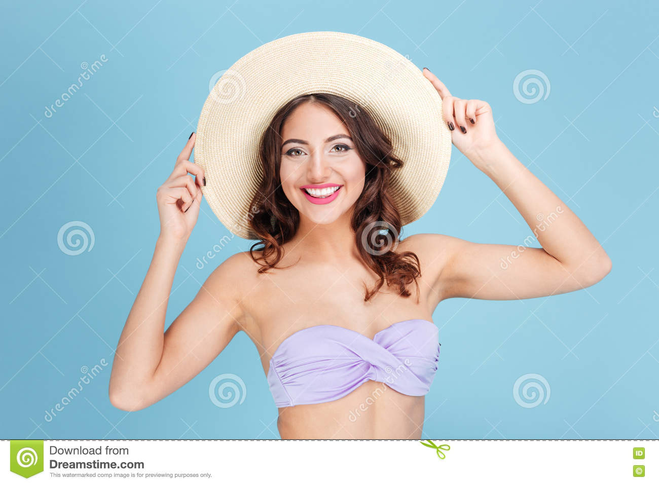 00d18a10705bf Close-up portrait of a cheerful pretty girl in a beach hat and swimsuit  isolated on the blue background