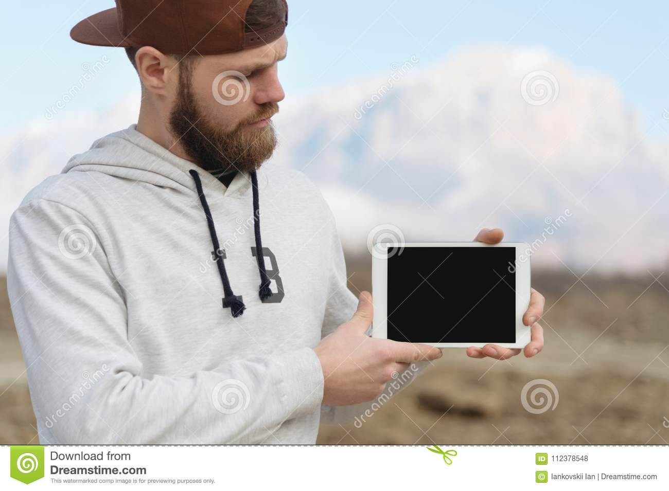 Close-up Portrait of a hipster in a brown cap in the open air holds a white tablet pc in his hands. A bearded man looks