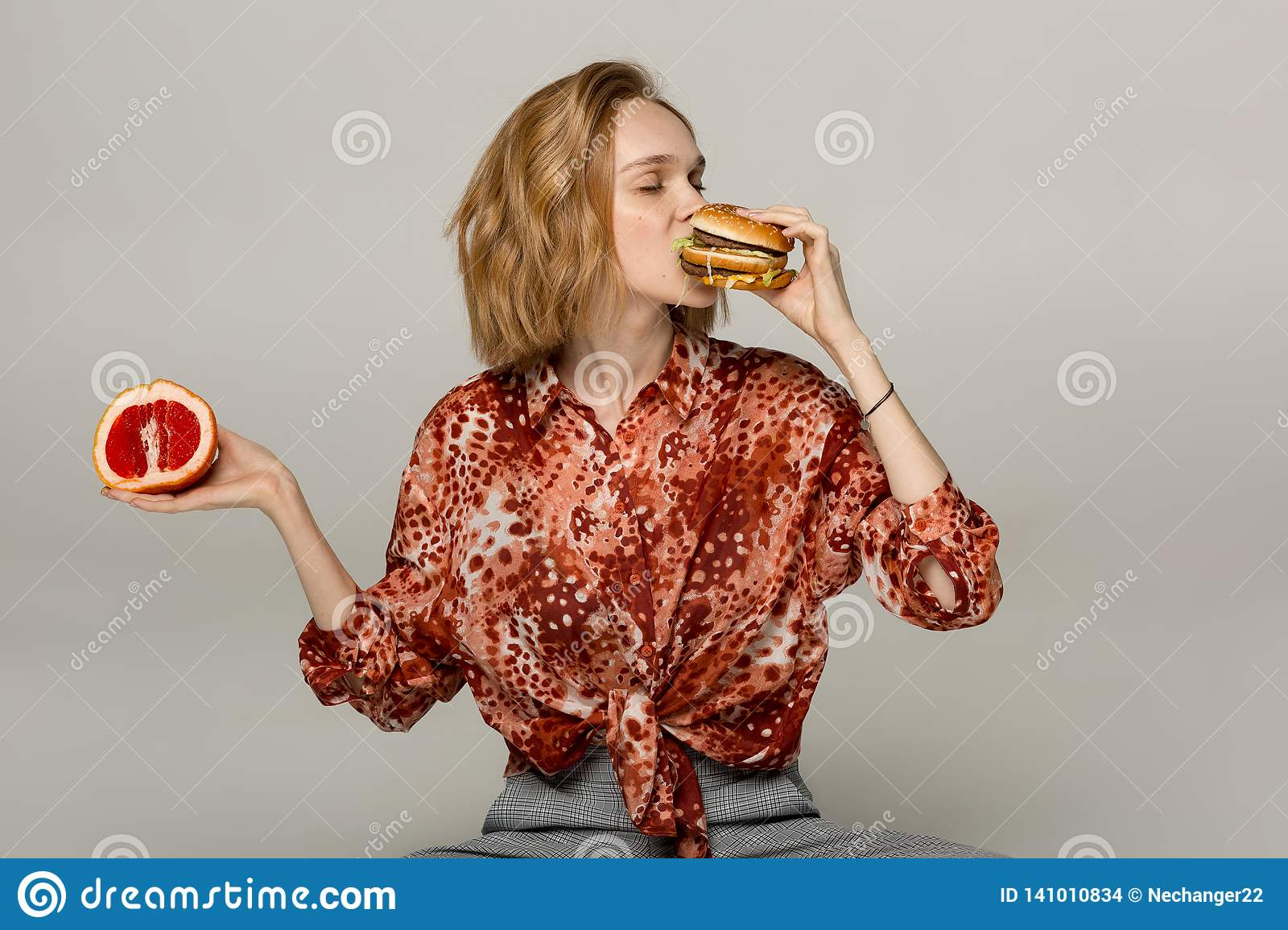 Close up portrait of pretty blonde girl that eating burger