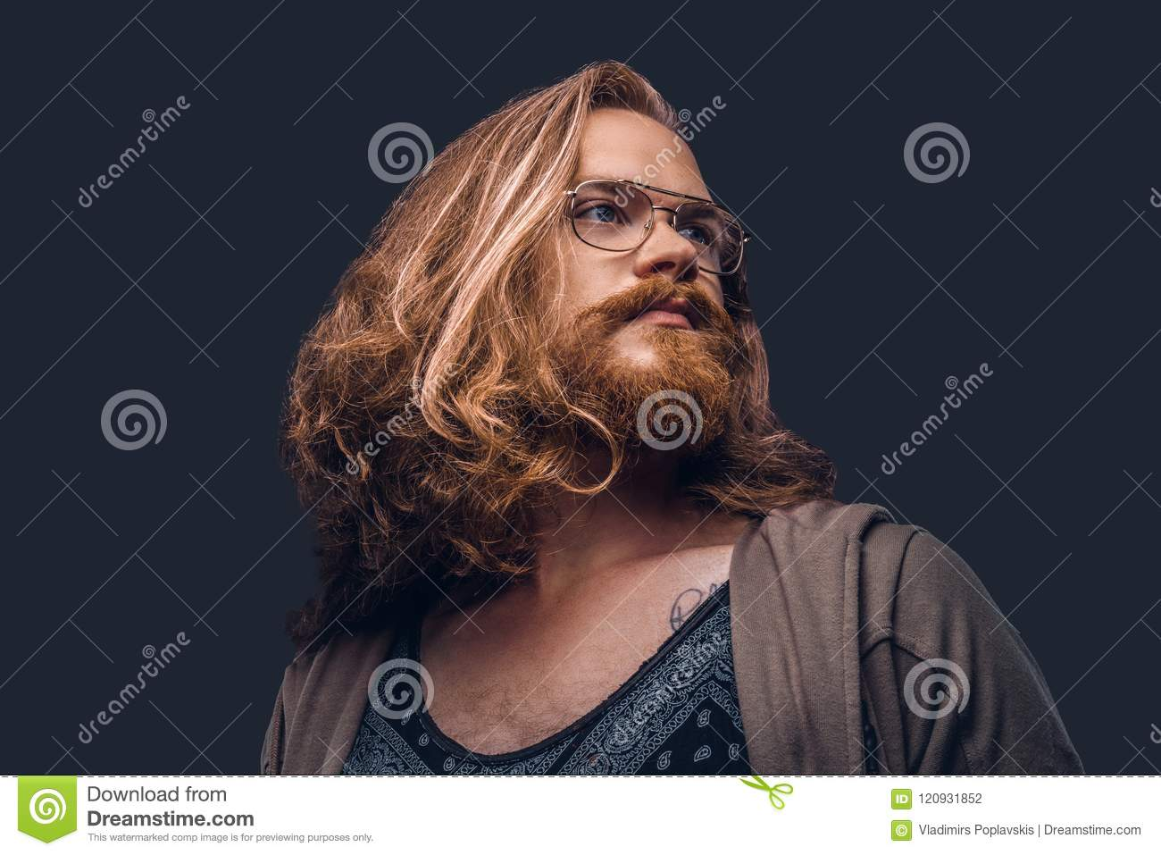 Close-up portrait of a redhead hipster male with long luxuriant hair and full beard dressed in casual clothes standing