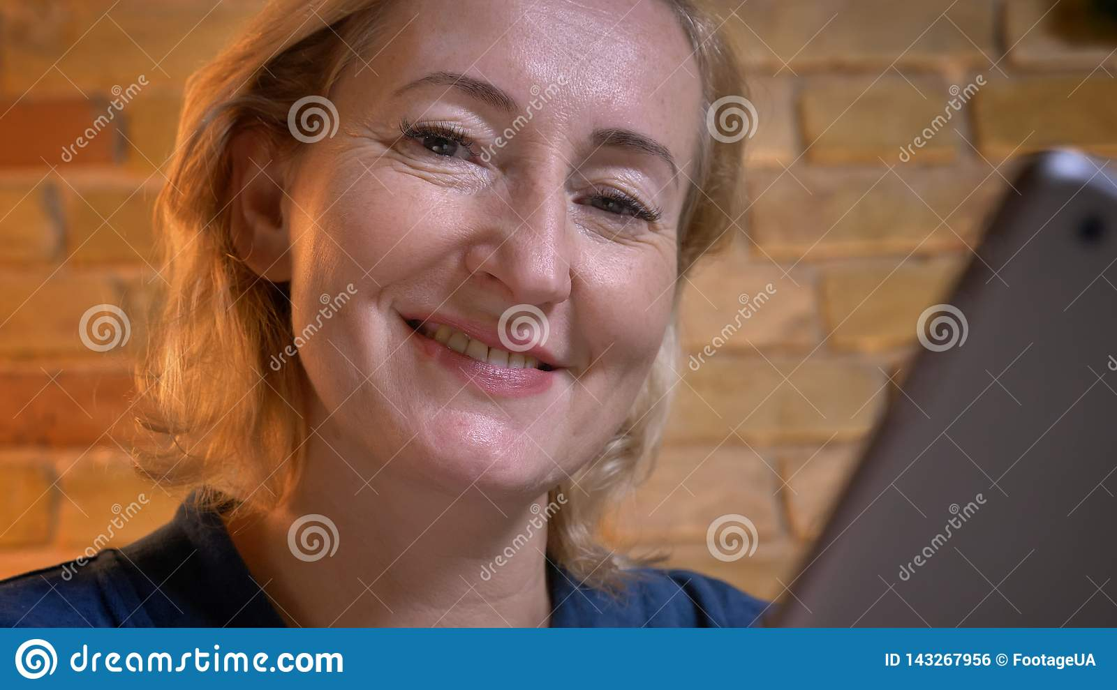 Close-up portrait of senior caucasian lady working with tablet and watching into camera smilingly in cozy home