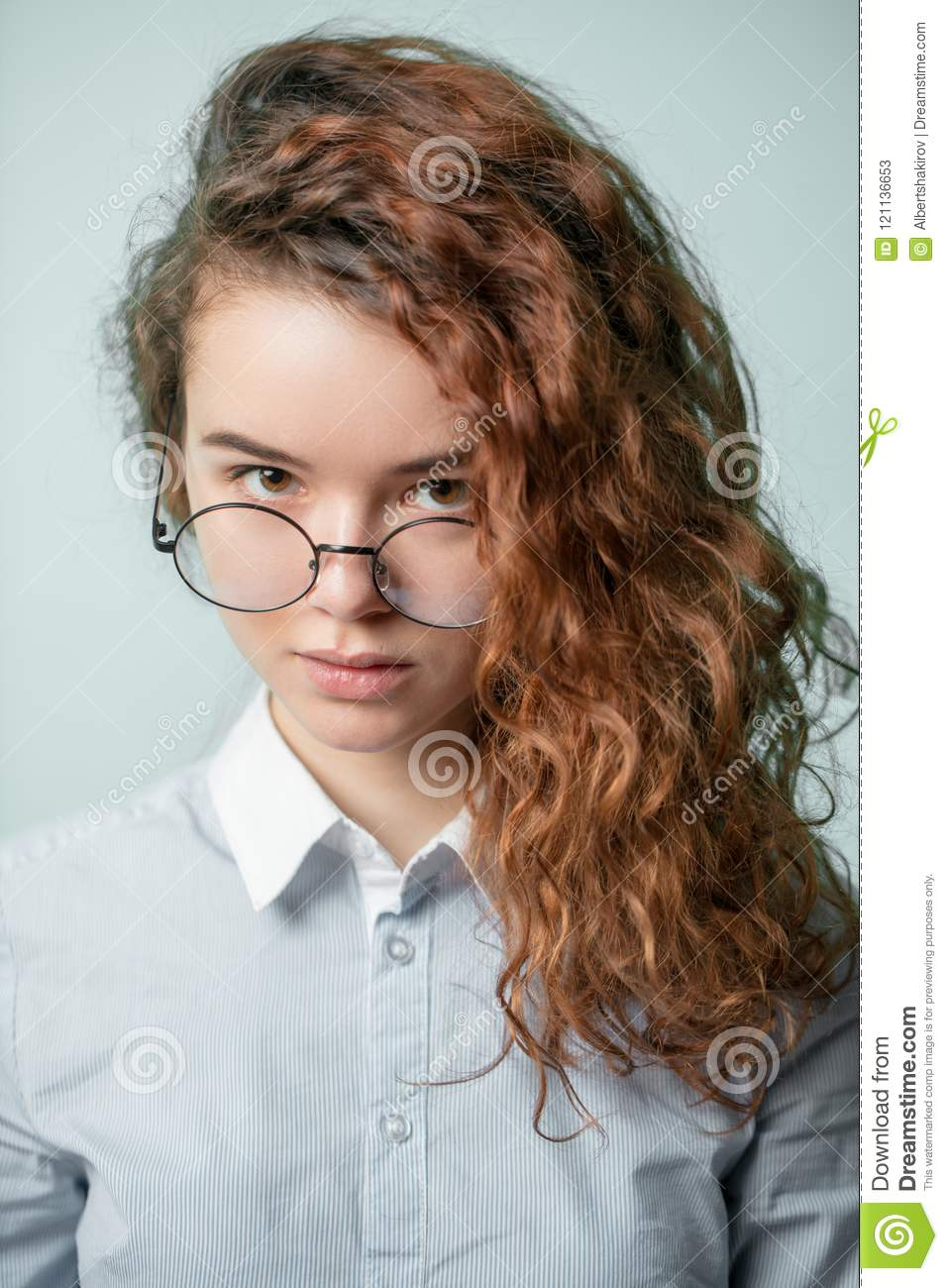 Close Up Portrait Of Serious Girl With Long Red Curly Hair Stock
