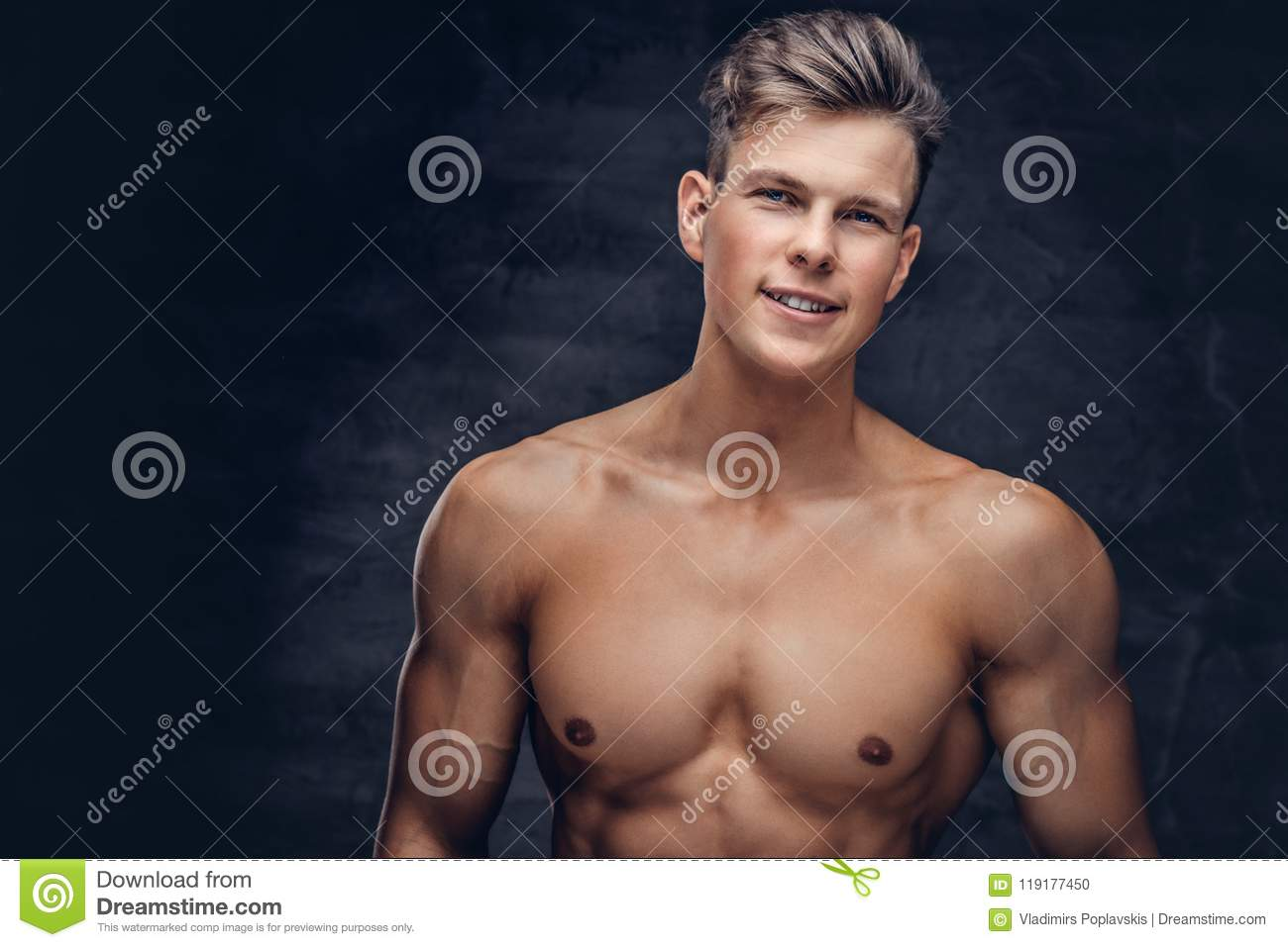 Close-up portrait of a shirtless young man model with a muscular body and stylish haircut posing at a studio