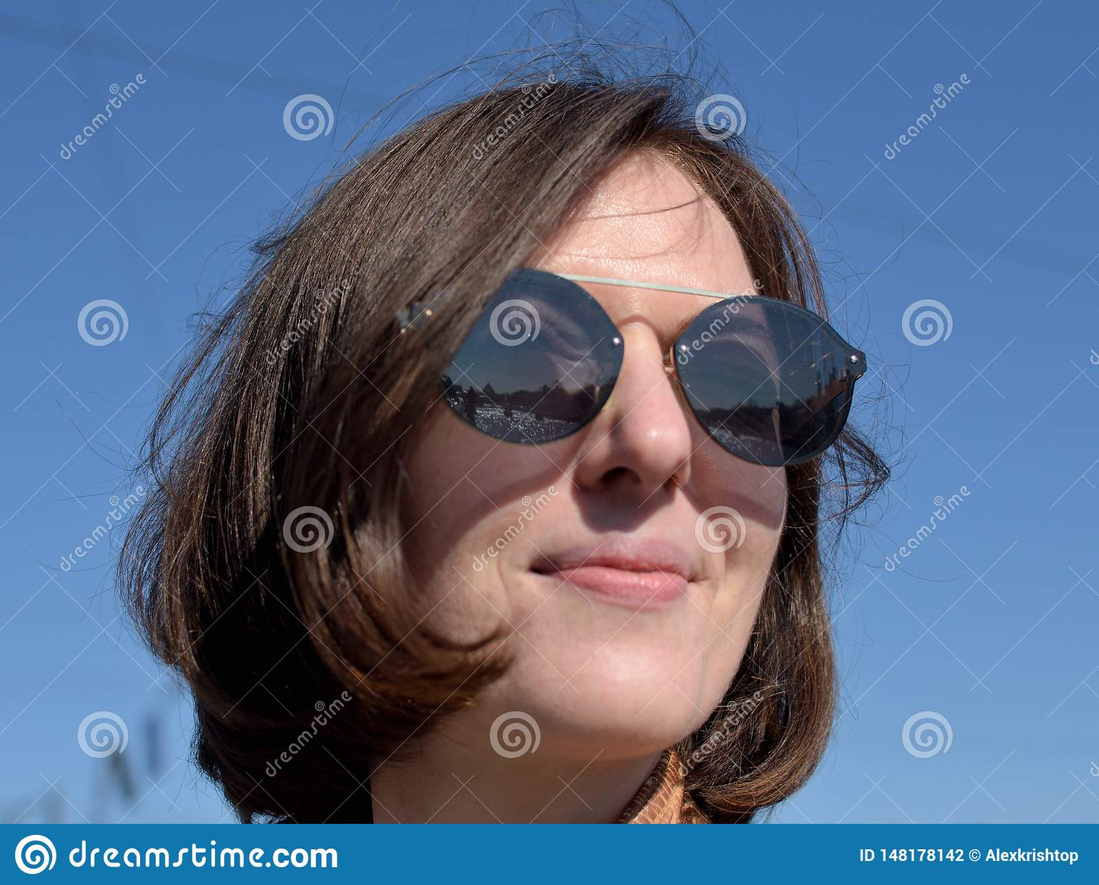 Close-up portrait of a smiling young lady tourist in Saint Petersburg Russia wearing sunglasses