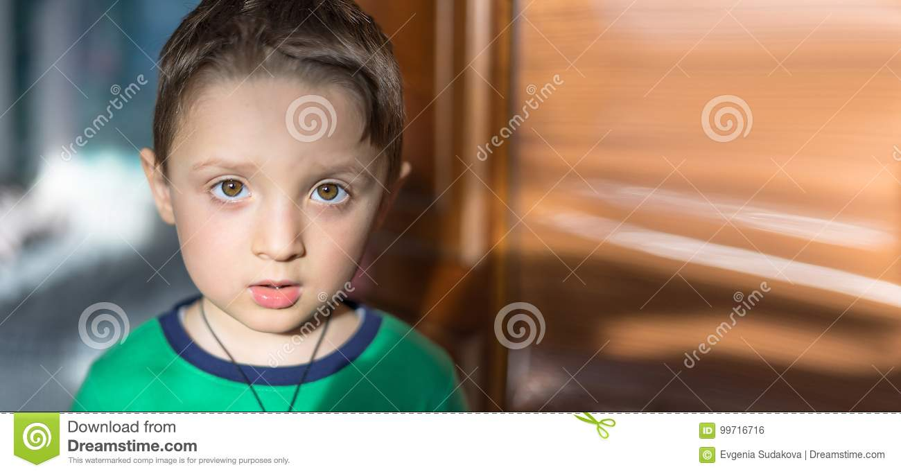 Close up portrait of a surprised european baby boy looking at camera over light background