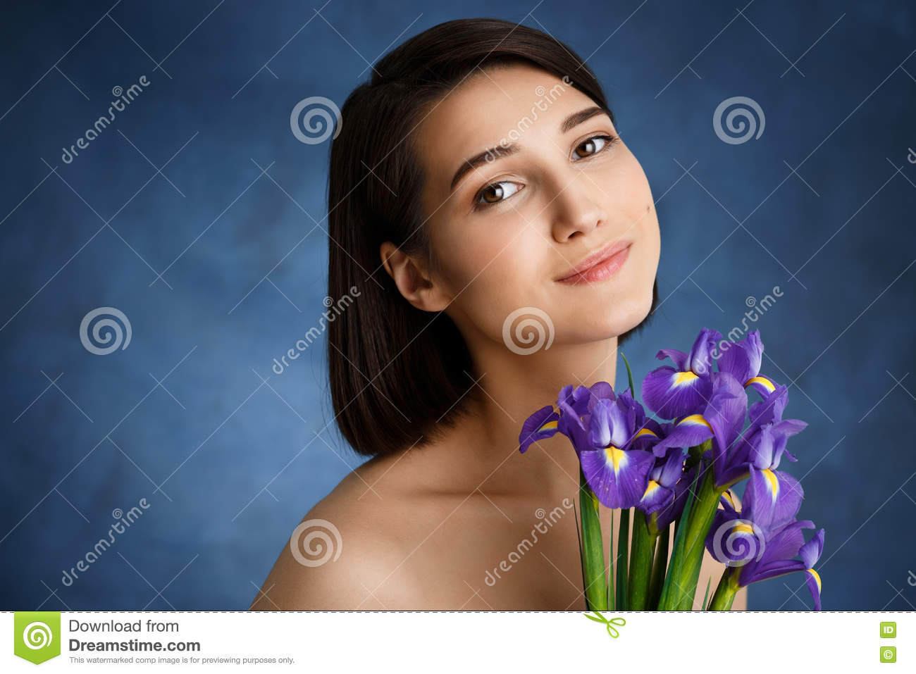 Close up portrait of tender young girl with violet irises over blue background