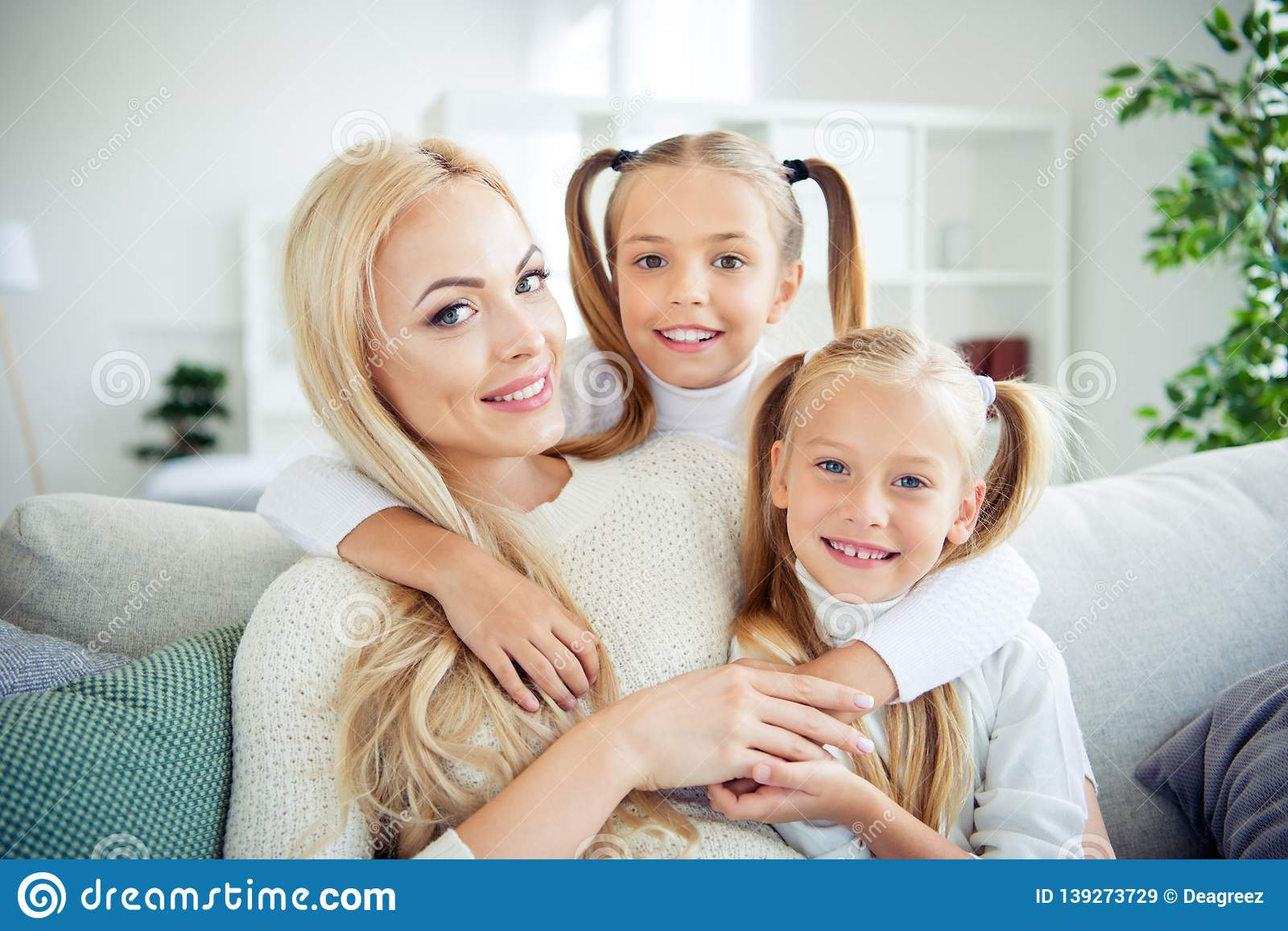 Close-up portrait of three nice cute lovely lovable attractive winsome  cheerful positive people pre-teen girls cuddling delicate mom mum mommy in  light ...