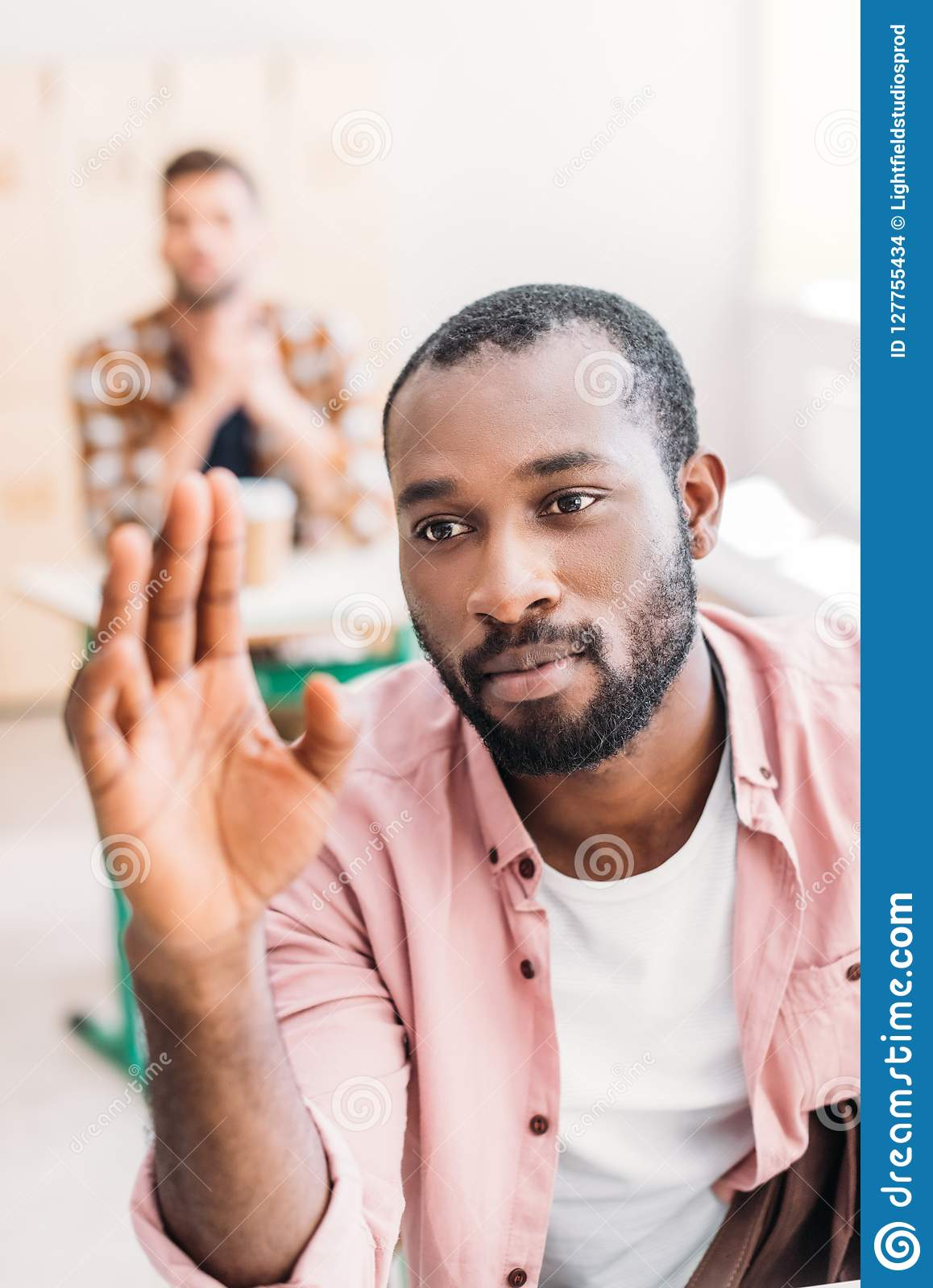 close-up portrait of young african american student raising hand to answer