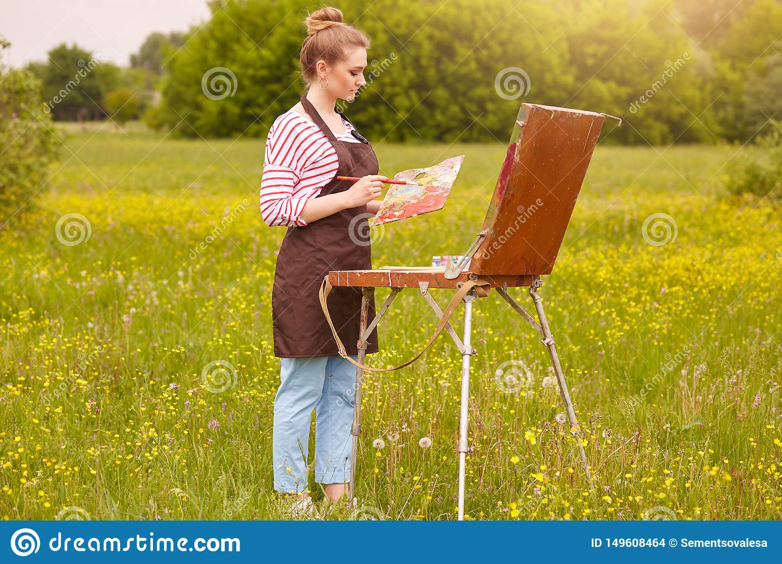Close up portrait of young attractive artist in open air, being good at oil painting. Cute lady drawing landscape, likes to