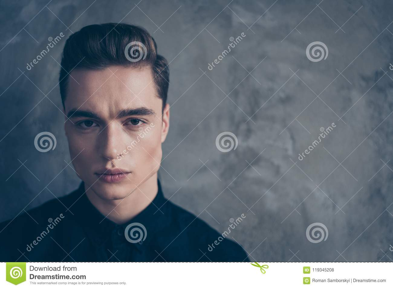 f6b3dfdf7cc Close up portrait of young attractive serious guy in black shirt looking  straight in the camera, behind is grey background