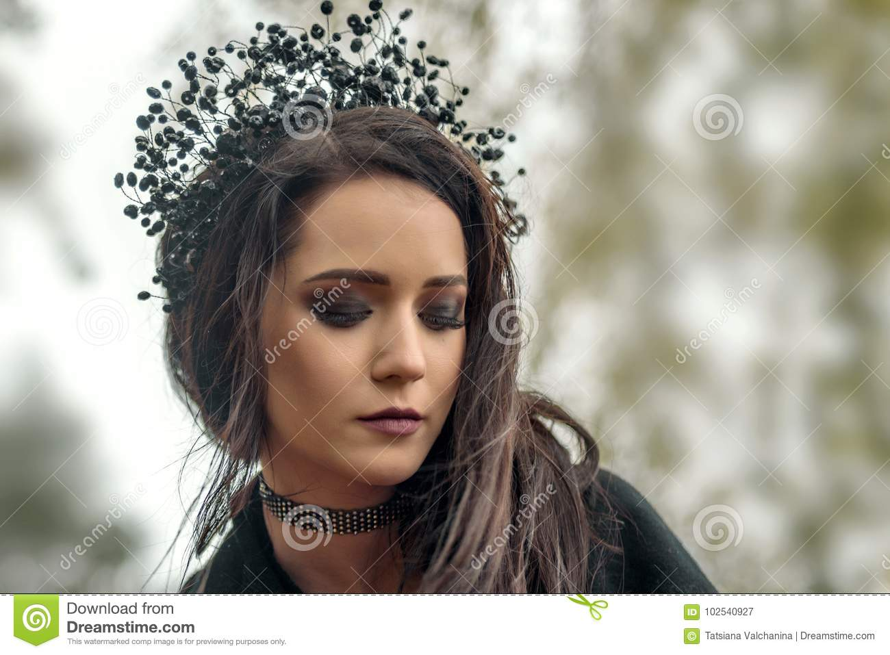 close up portrait of a young girl in the image of the black queen witch in a black crown tiara