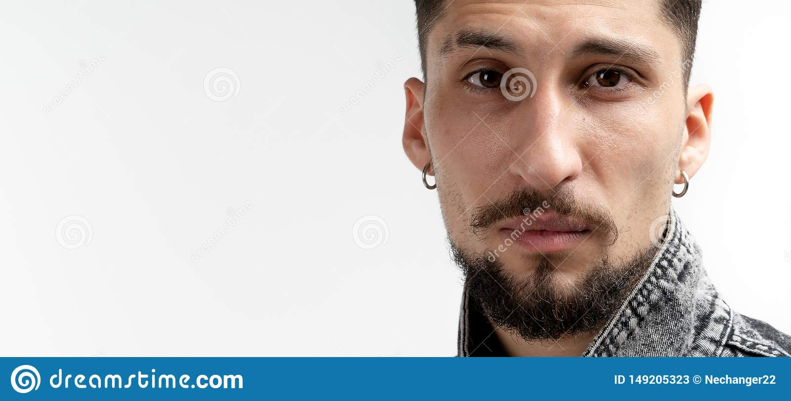 Close up portrait of young serious bearded man in denim shirt that looking at the camera isolated over white background
