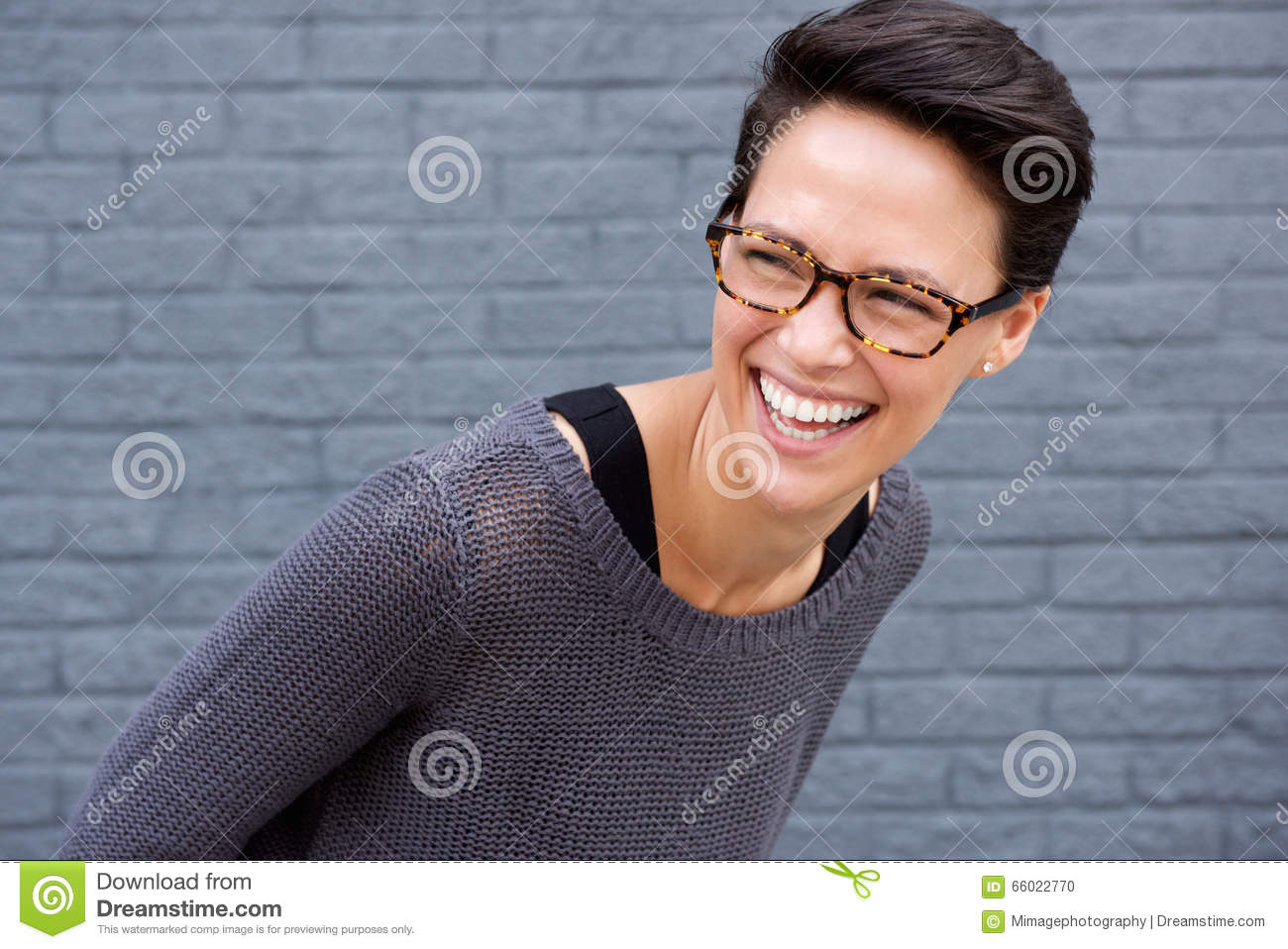 Close up portrait of a young woman laughing with glasses