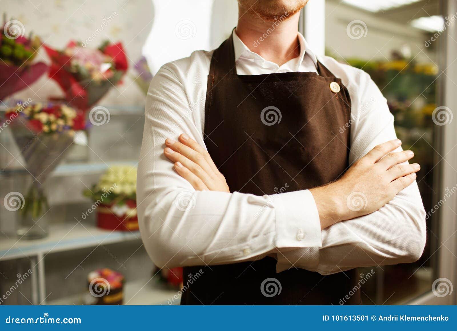 Close-up of a confident florist in a brown apron on a shop background. Florist uniform concept.