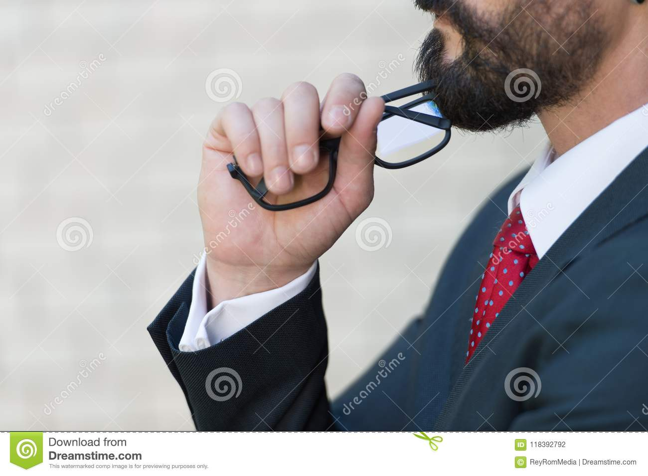 Close up profile of bearded businessman and hand holds glasses. Man in blue suit and red tie thinking over new idea.