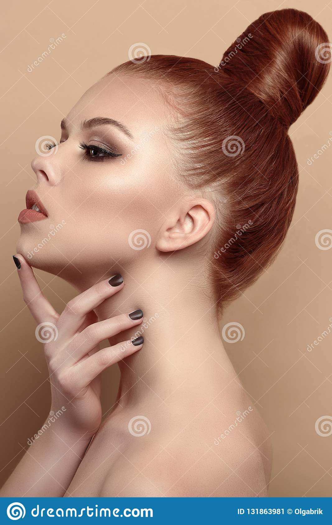 Close up profile portrait of beautiful red-haired model with her hair scraped back into a high bun
