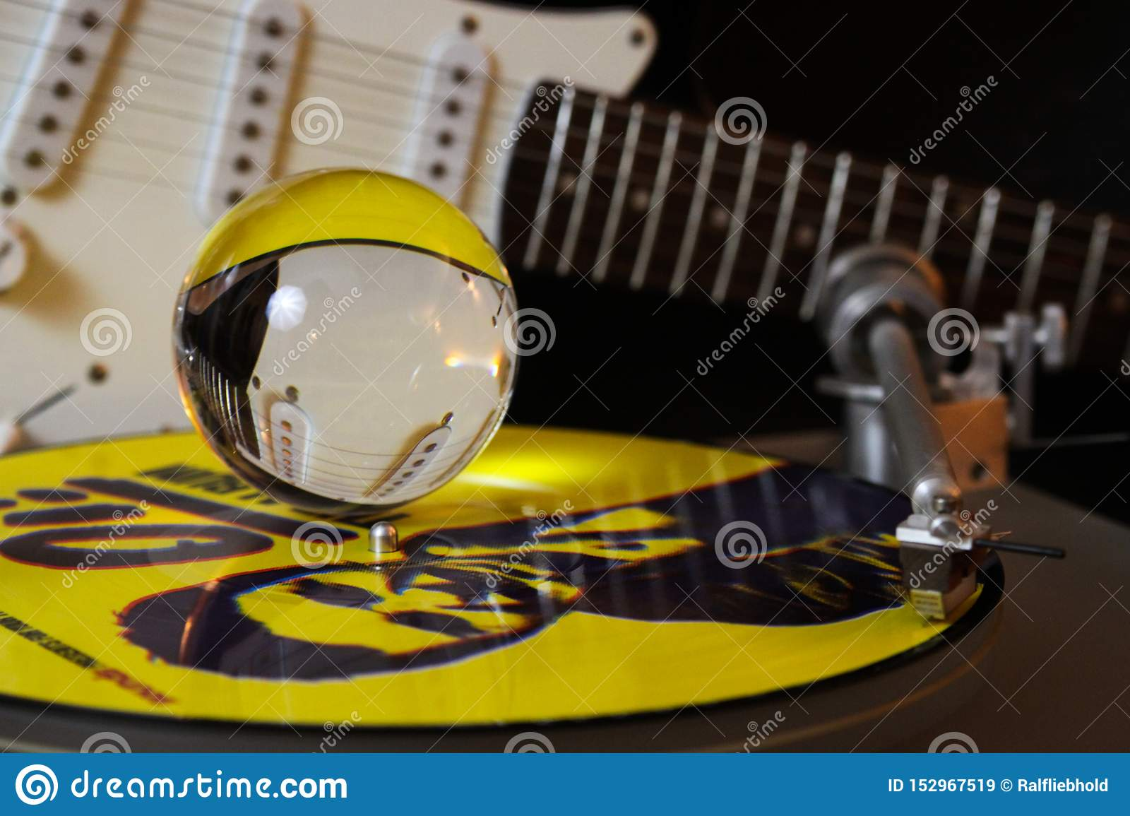 Close up of record player with yellow punk vinyl LP and crystal sphere glass ball und blurred electric guitar with black