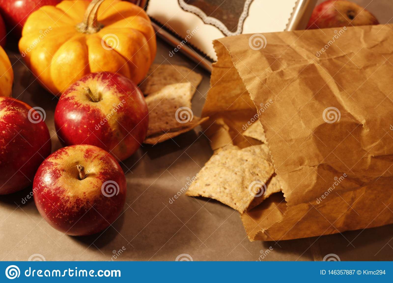 Close up on red apples and a paper bag of crispbread