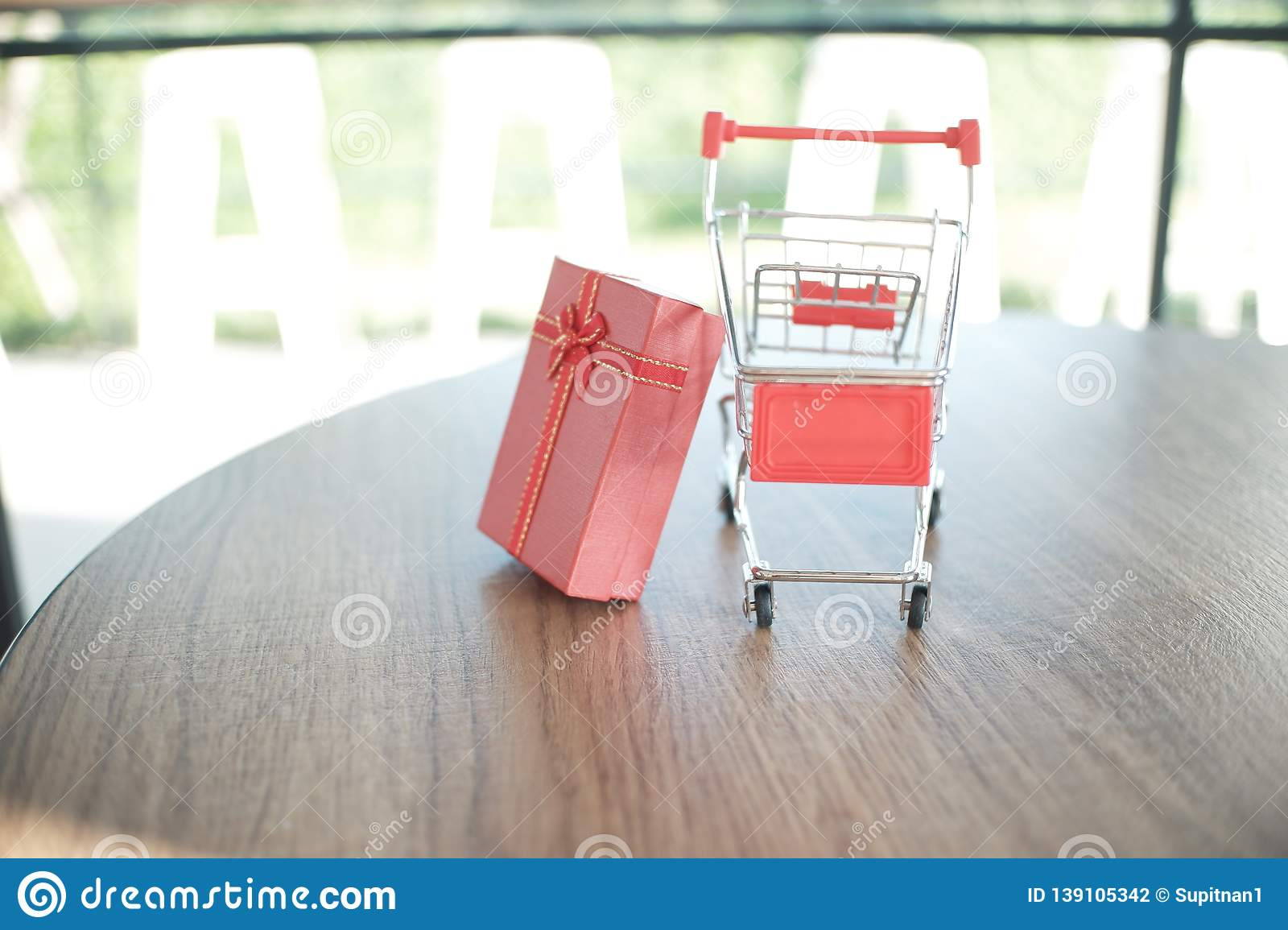 Close up red gift box and shopping cart on table for shopping and e-commerce concept
