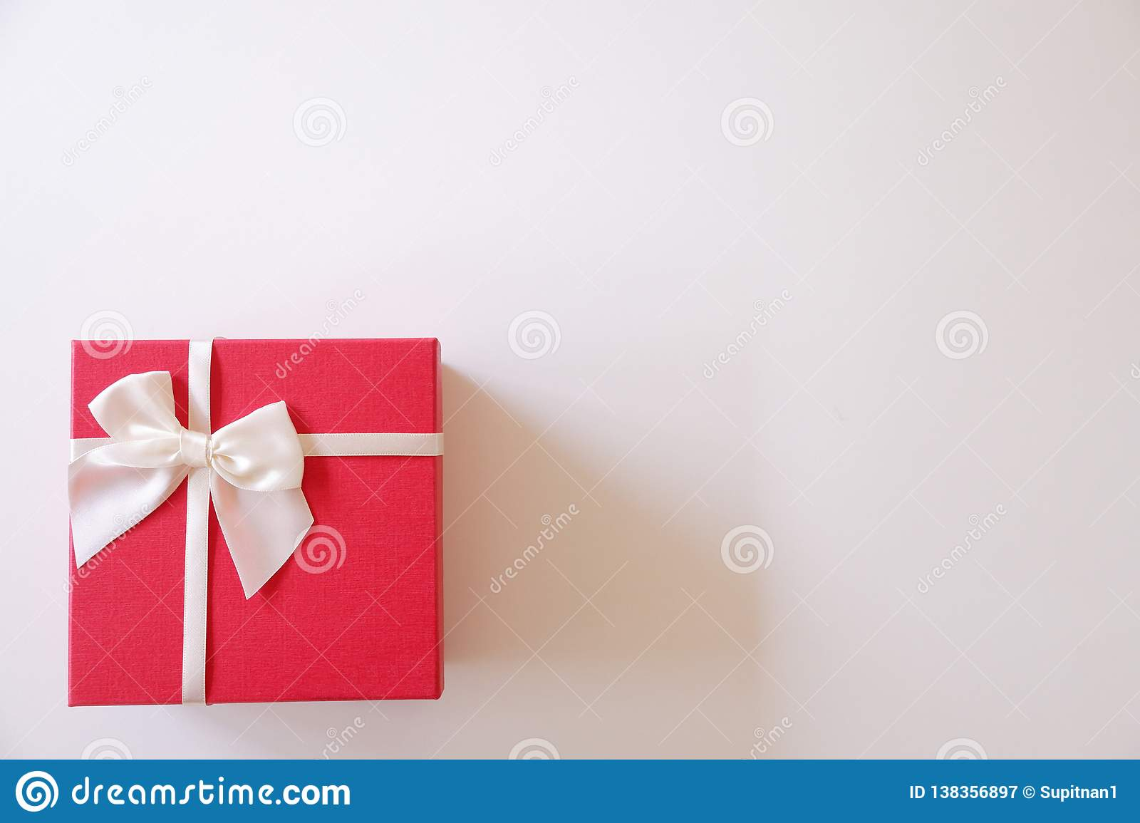 Close-up red gift box with white ribbon on white background