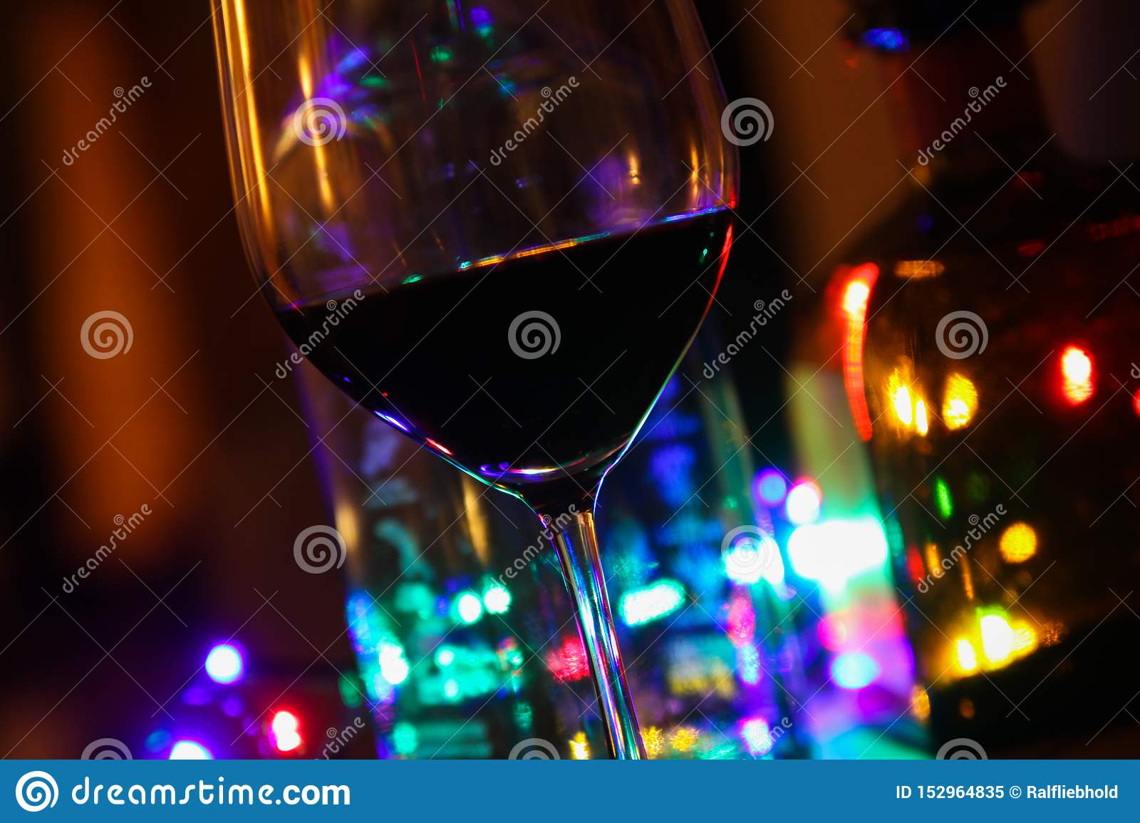 Close up of red wine glass with bottles of alcohol and colorful electric light