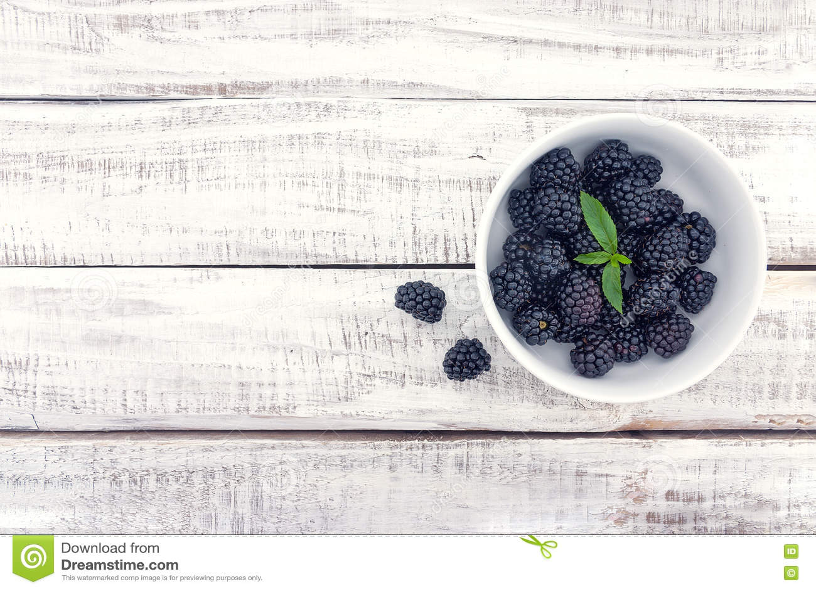 Close up of ripe blackberries in a white ceramic bowl over rusti