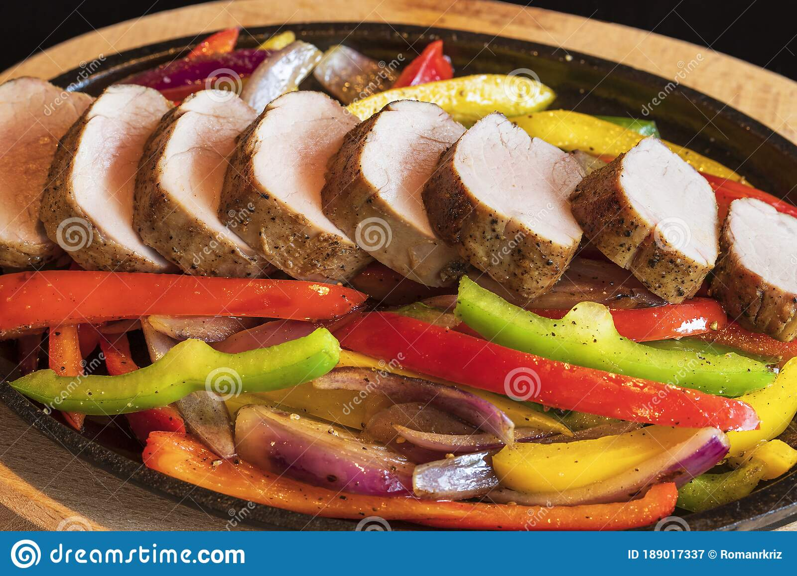 Close Up Of Roasted Pork Tenderloin Medallions With Grilled Vegetables On A Hot Pan The Food Is Isolated On A Black Background Stock Image Image Of Juicy Prepared 189017337