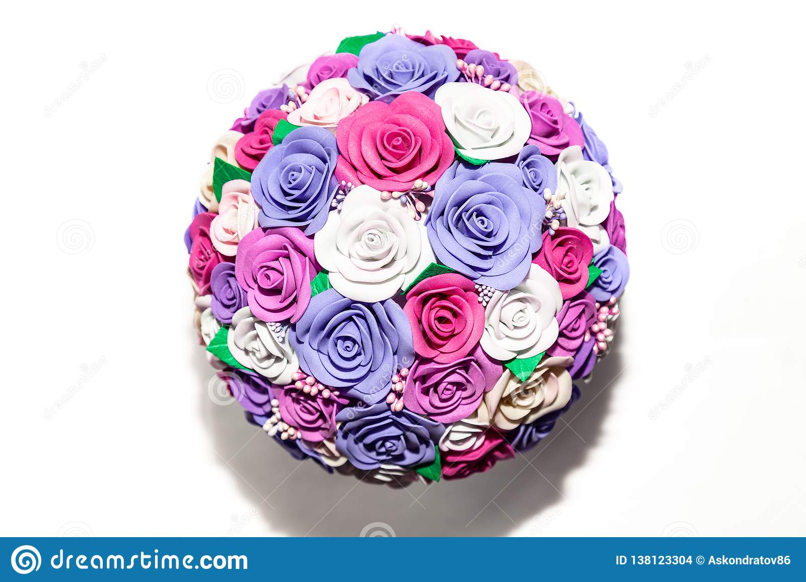 A close-up of a romantic artificial bouquet of flowers of a lilac, pink and white fabric on an empty background is a gift for a