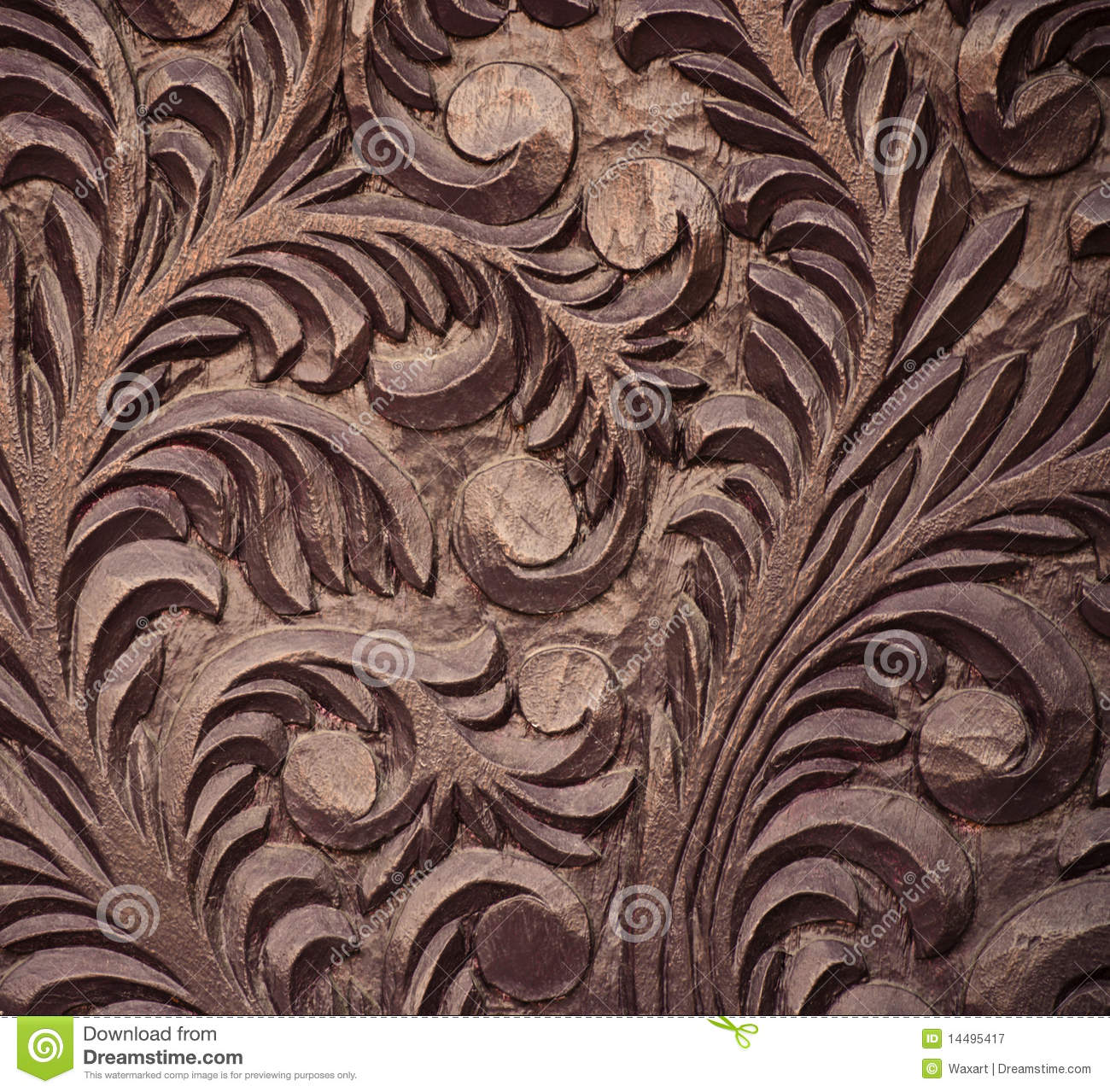 Brown wooden door with pattern of leaves and swirls in high relief