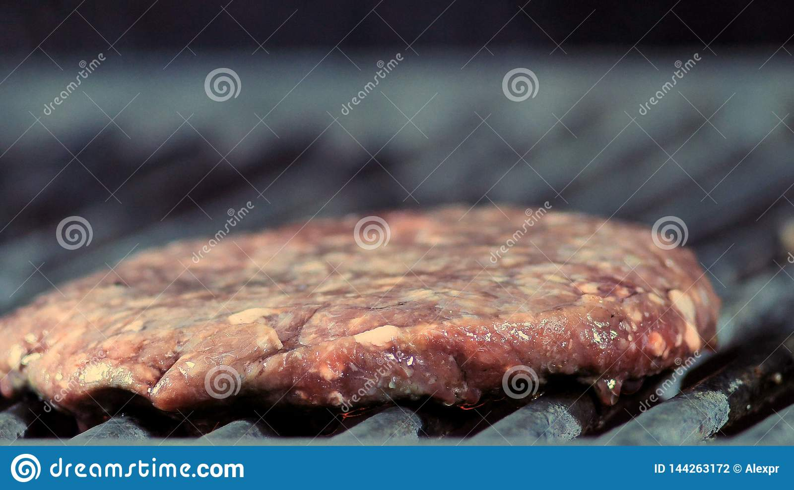 Close-up of a round burger patty is grilled and light smoke goes