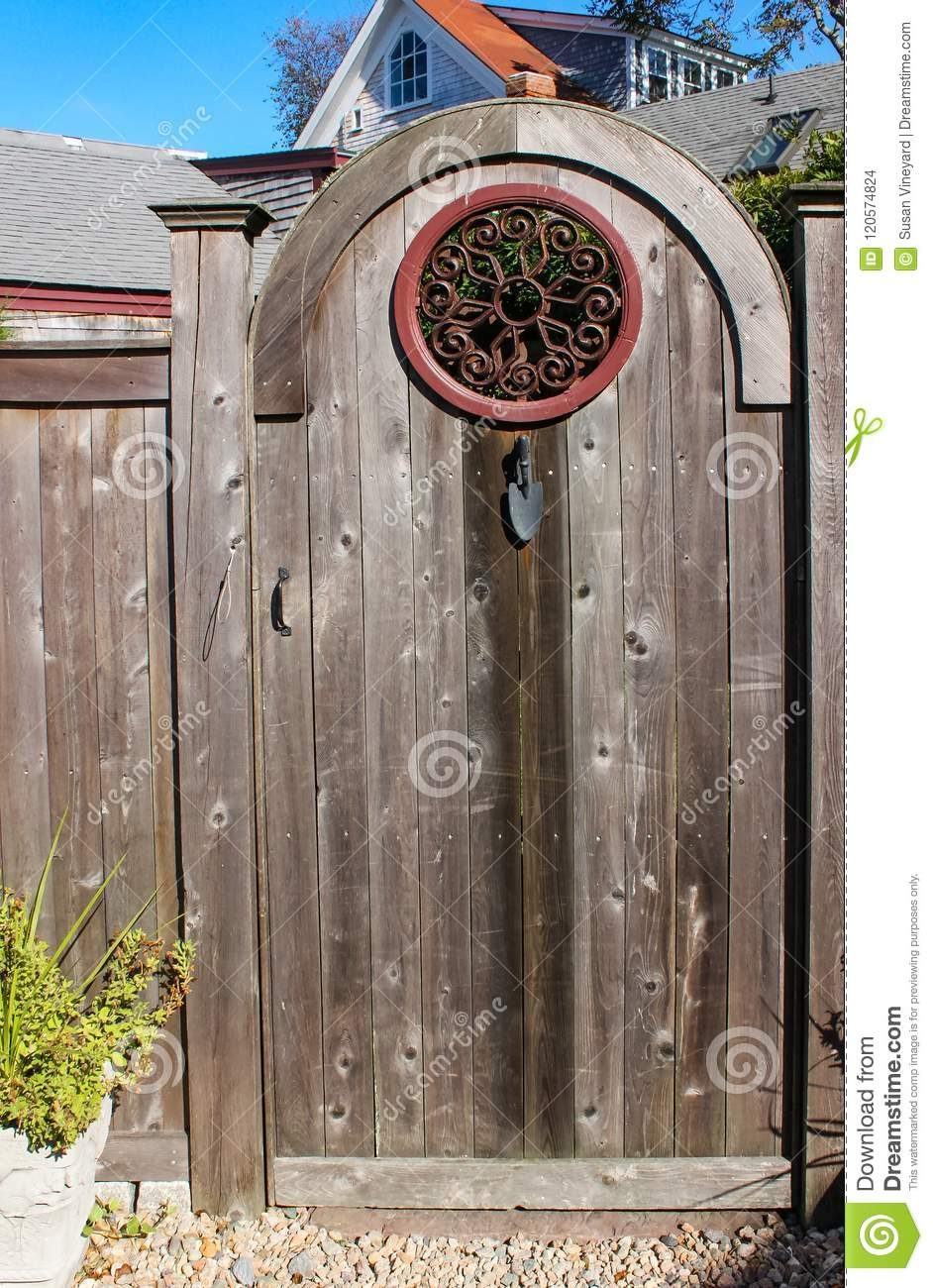 Close Up Of Rustic Wooden Gate With Decorative Round Wrought Iron