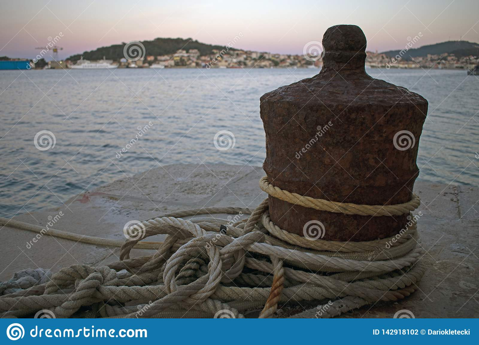 Close up of rusty boat mooring with ropes wrapped around
