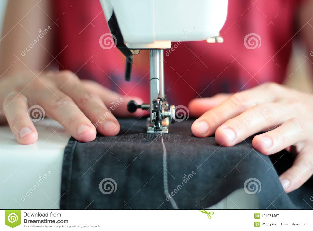 Close-up seamstress hands working on sewing machine at home. Sewing process. woman hands behind sewing close-up