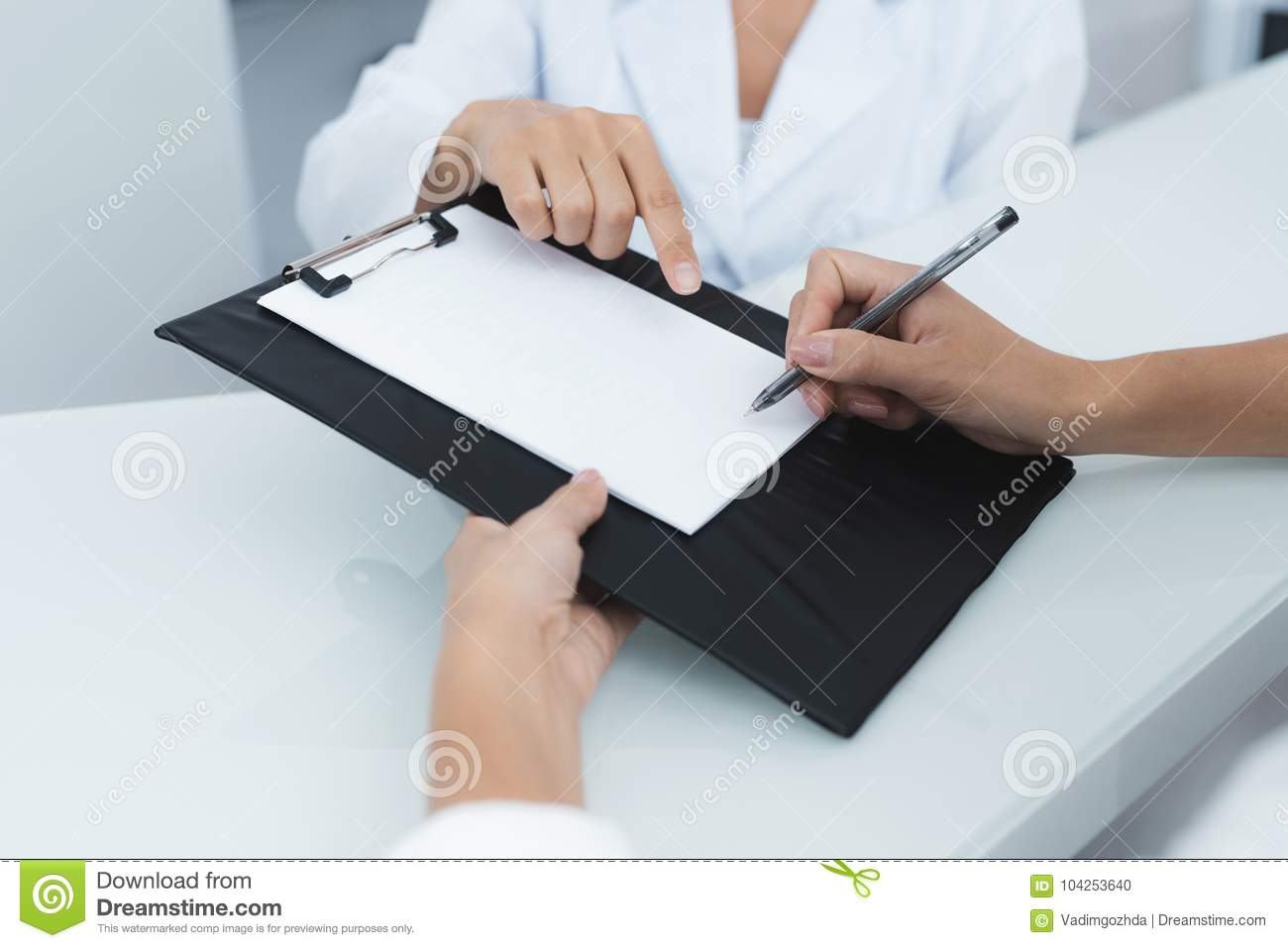Close up. The secretary in a medical clinic helps the patient complete the necessary forms before starting treatment.