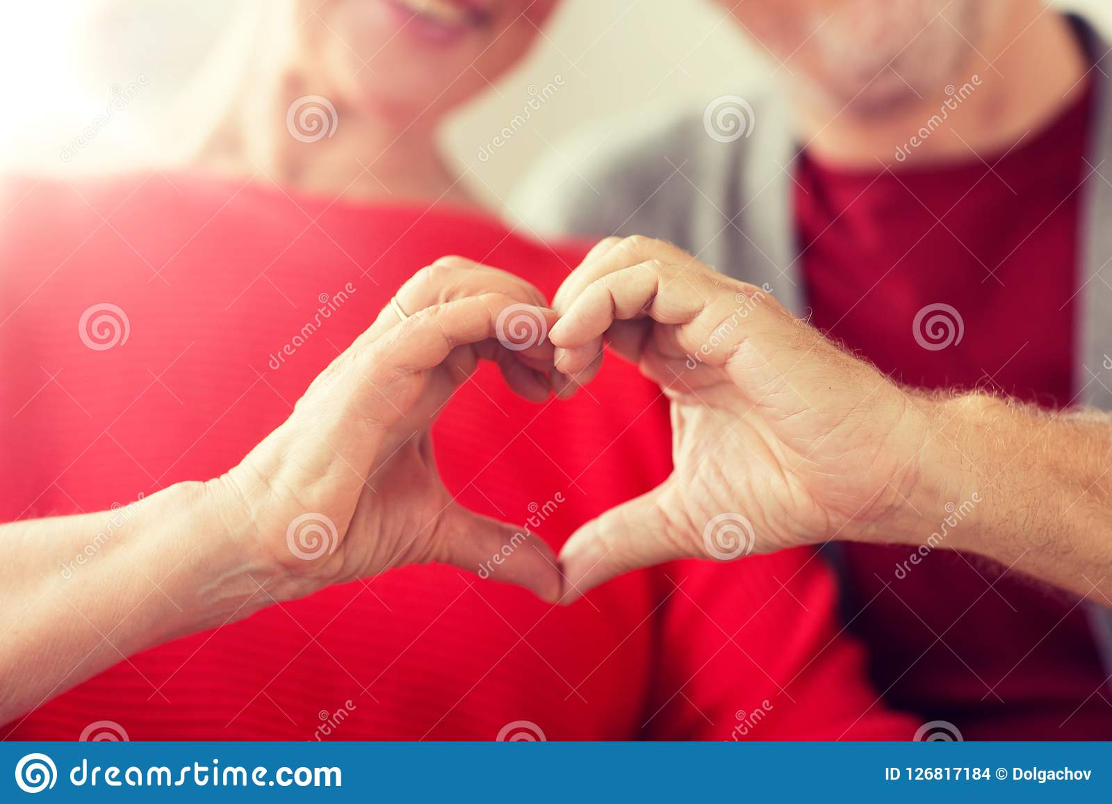 Close up of senior couple showing hand heart sign. Relationships, love and old people concept - close up of senior couple showing hand heart gesture Stock Images