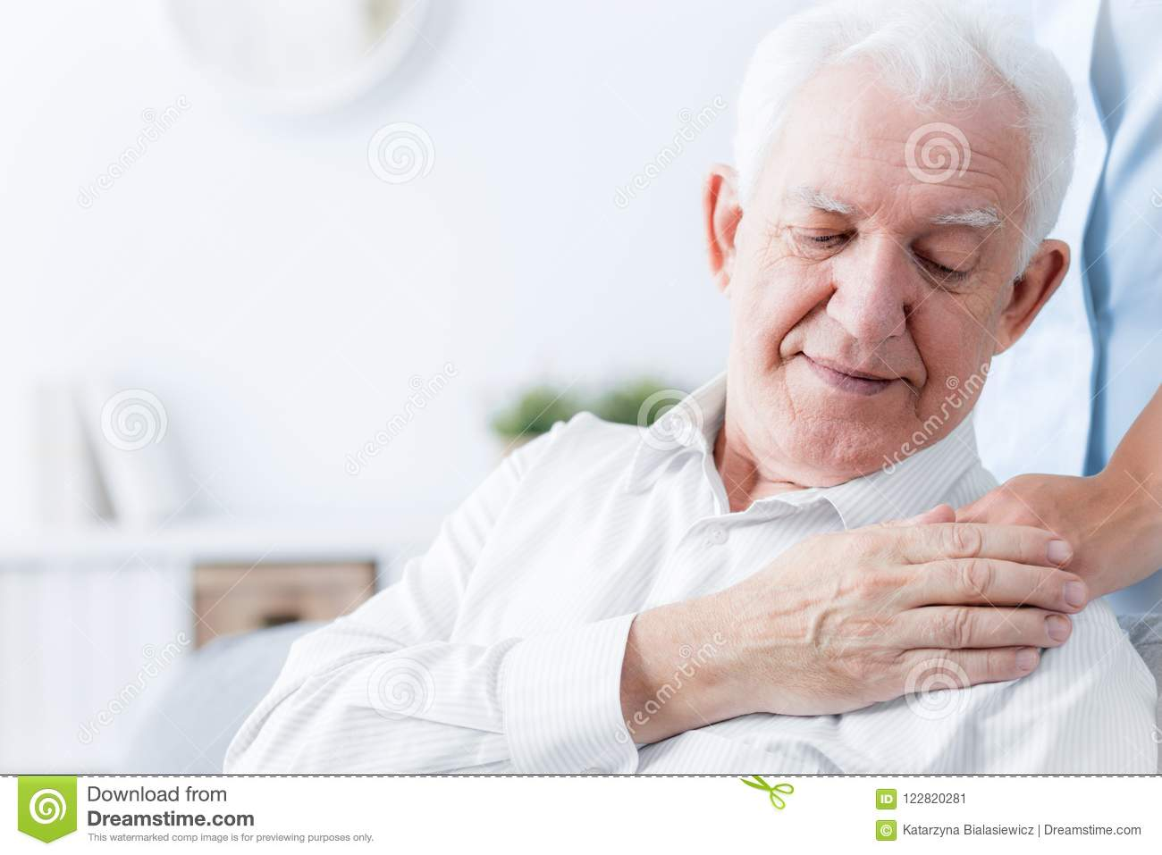 Close-up of senior man touching hand of friendly caregiver