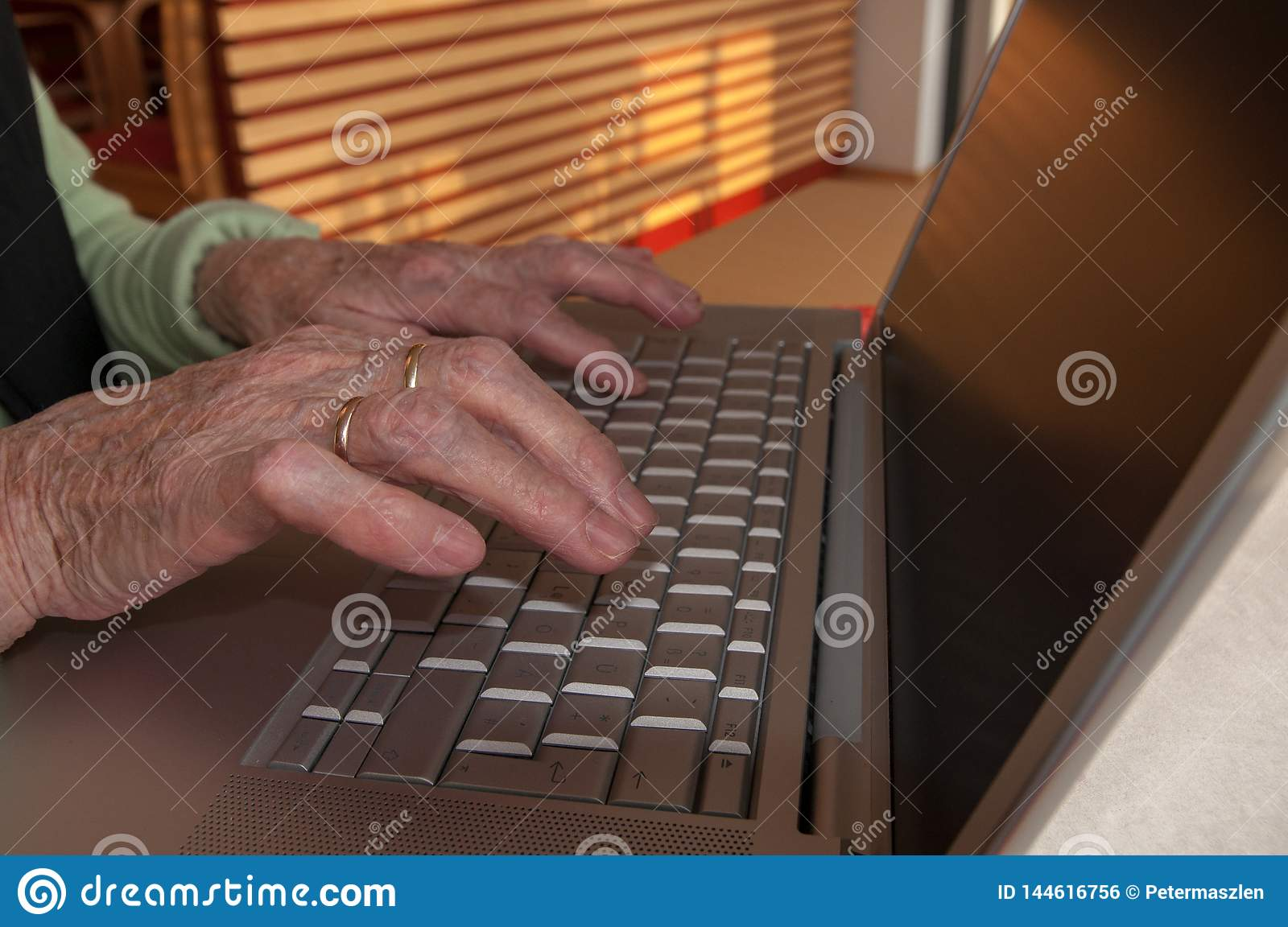 Close up of senior woman`s hands working on computer keyboard