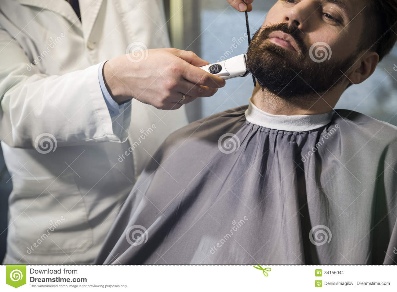 close up of a serious brown haired businessman having his beard combed and trimmed in a barber. Black Bedroom Furniture Sets. Home Design Ideas