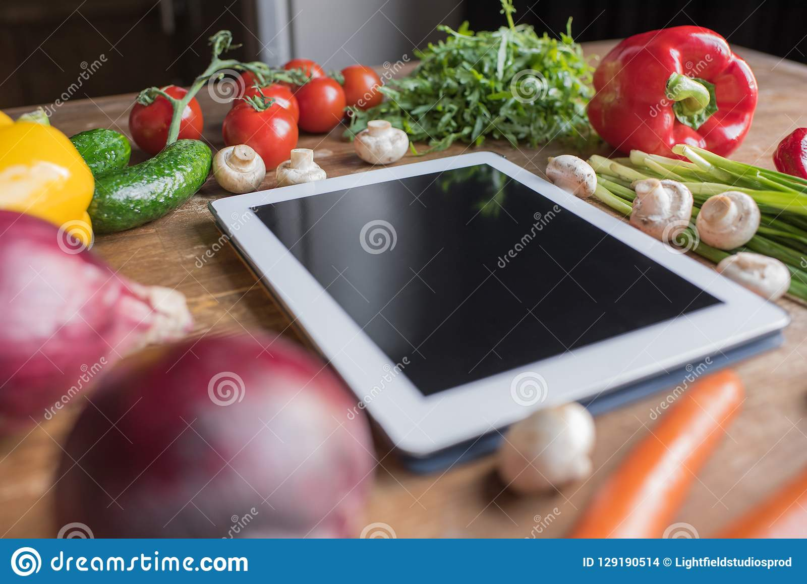 close-up shot of blank tablet with vegetables
