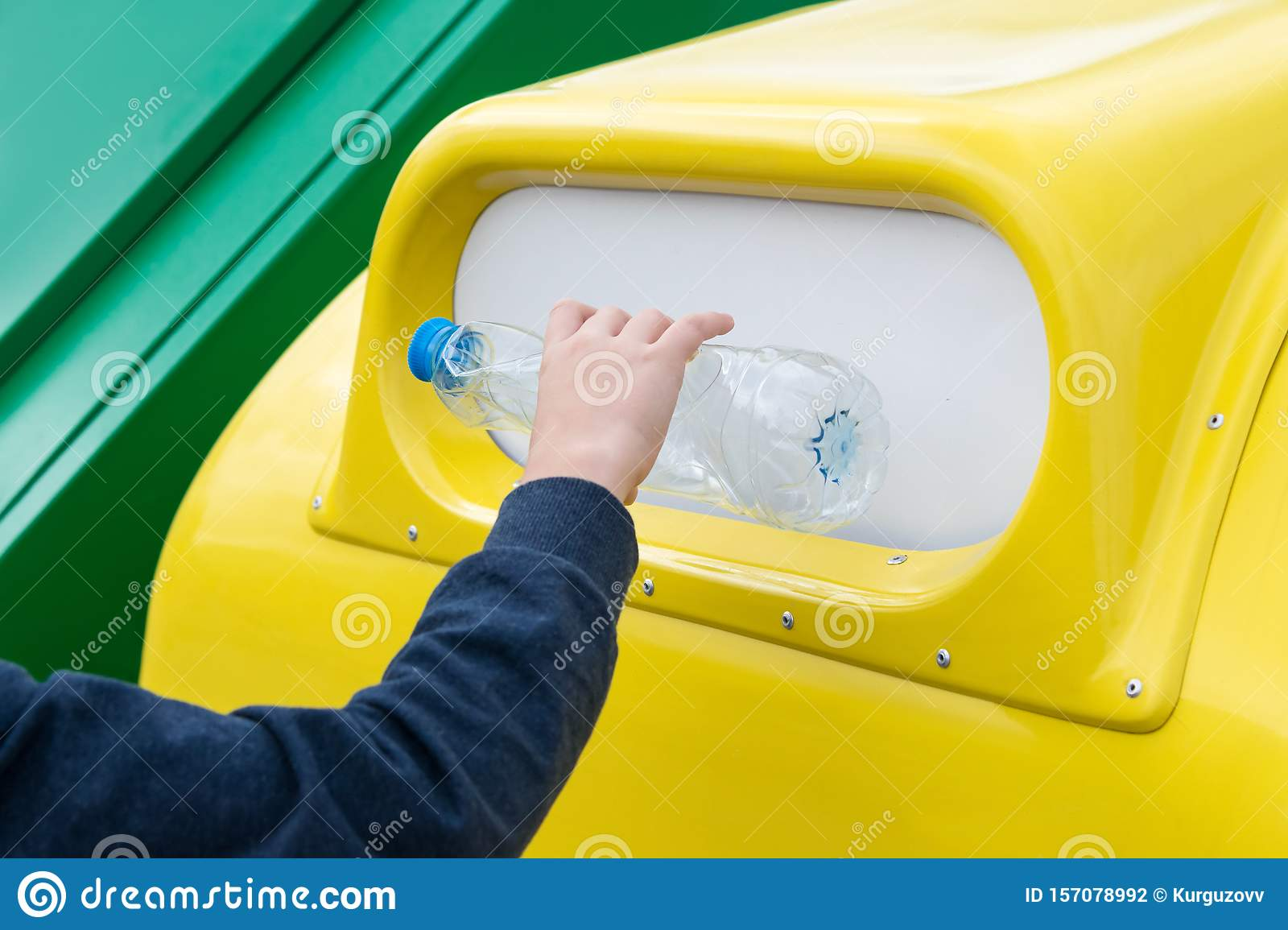 Close-up shot of a boy's hand throwing an empty plastic bottle into a separate garbage container