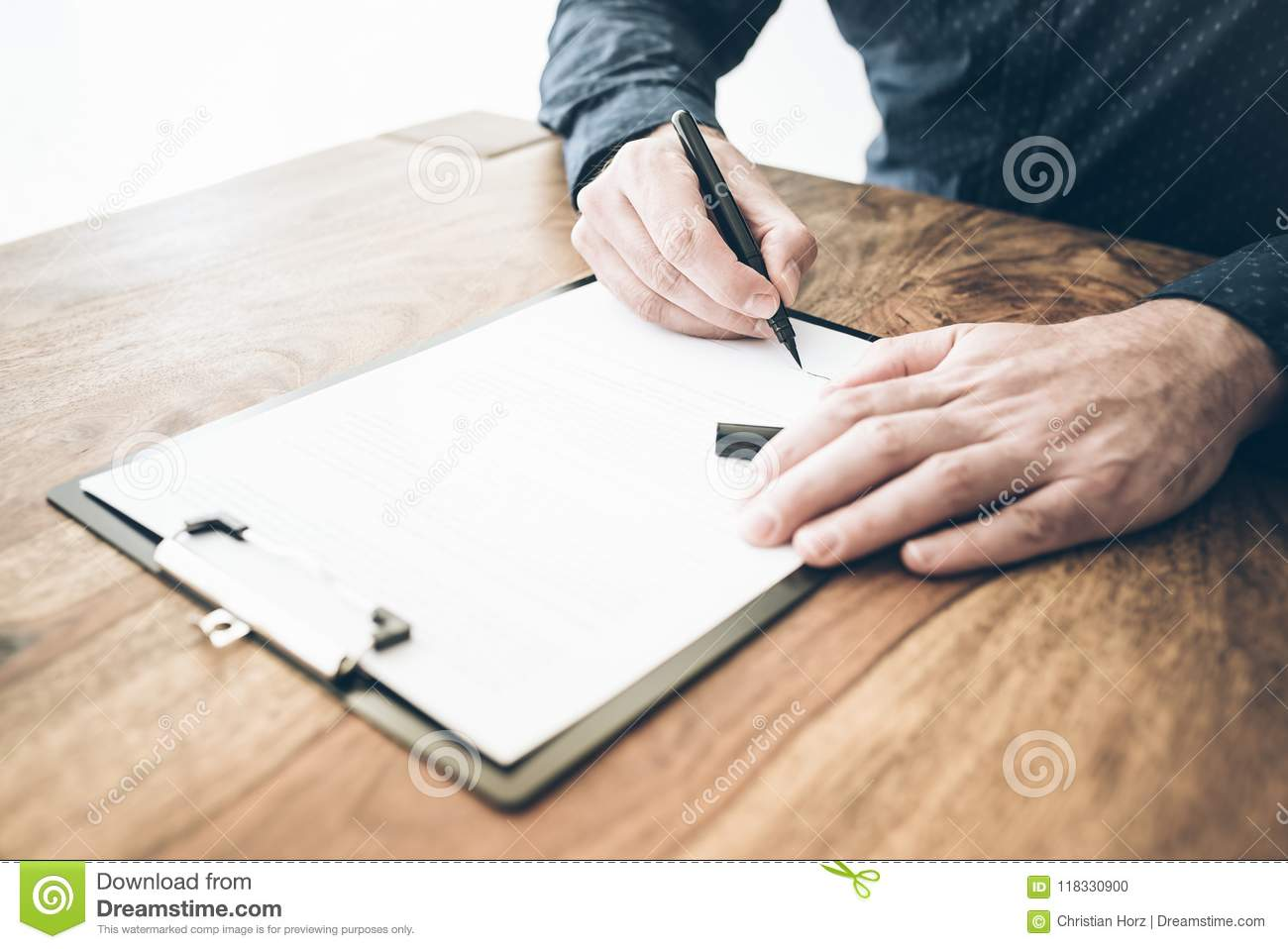 Close-up of businessman signing contract or document on wooden desk