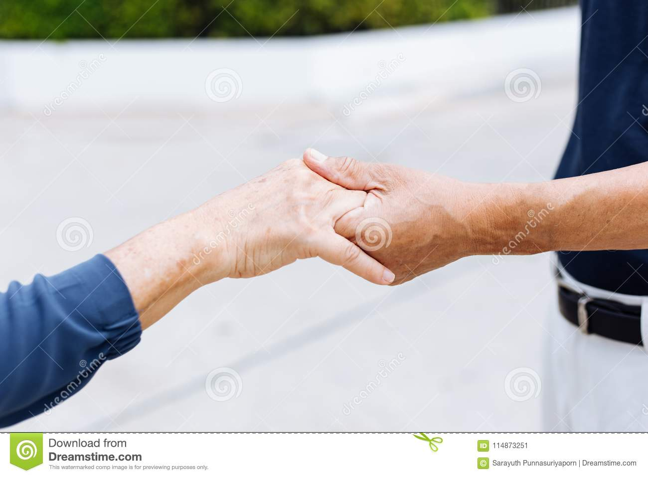 Close up shot of elderly senior couple holding hands and supporting with each other.